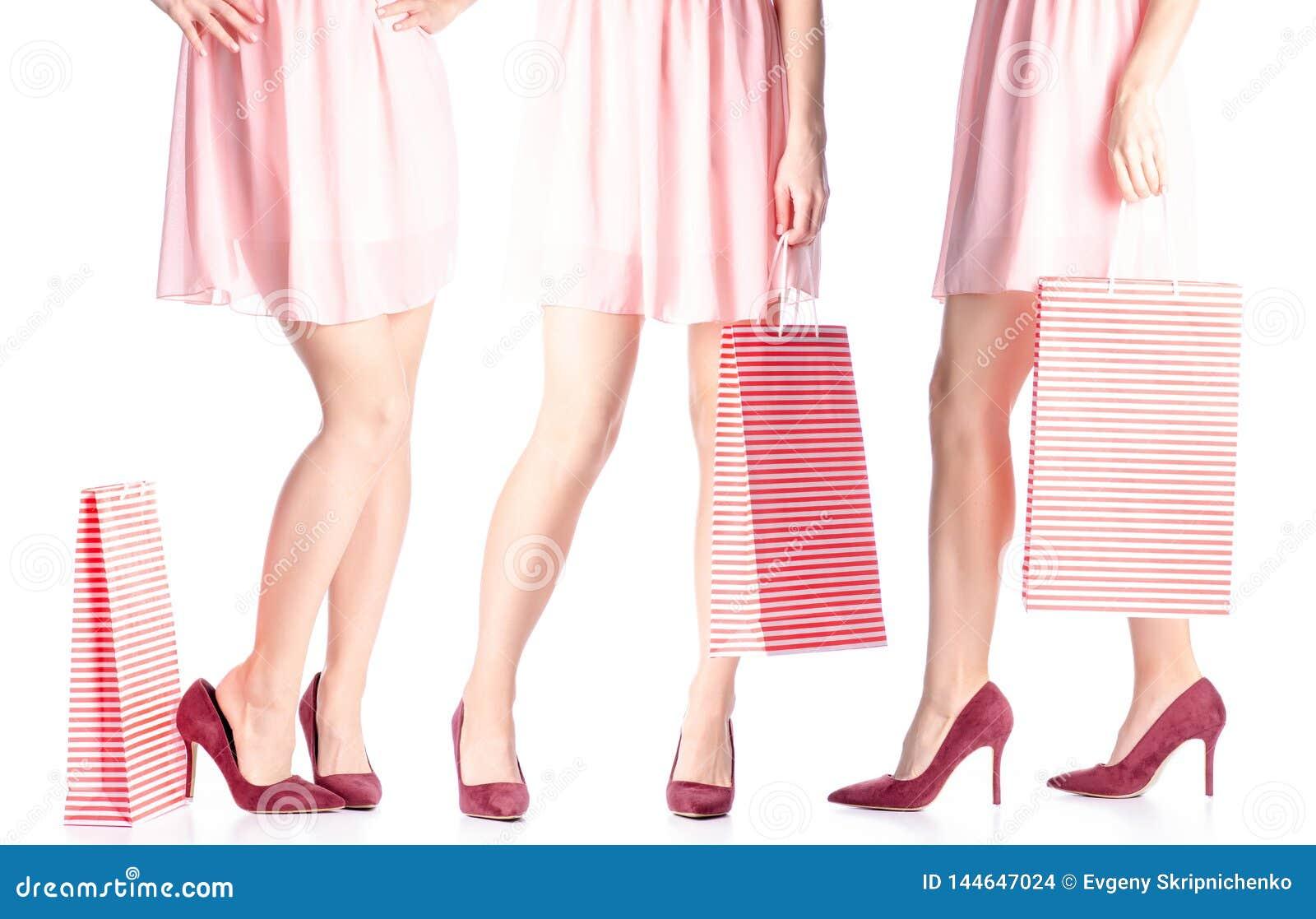 设置妇女腿以红色高跟鞋鞋子和礼服袋子包裹手中时尚