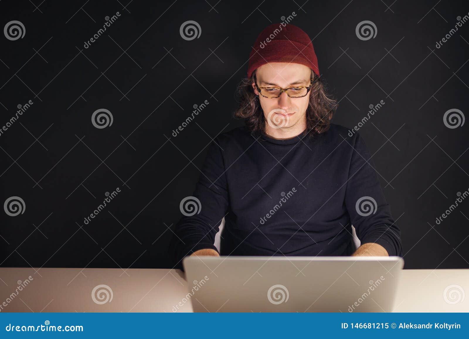 设计师或程序员在工作场所 坐在膝上型计算机的帽子和玻璃的年轻人