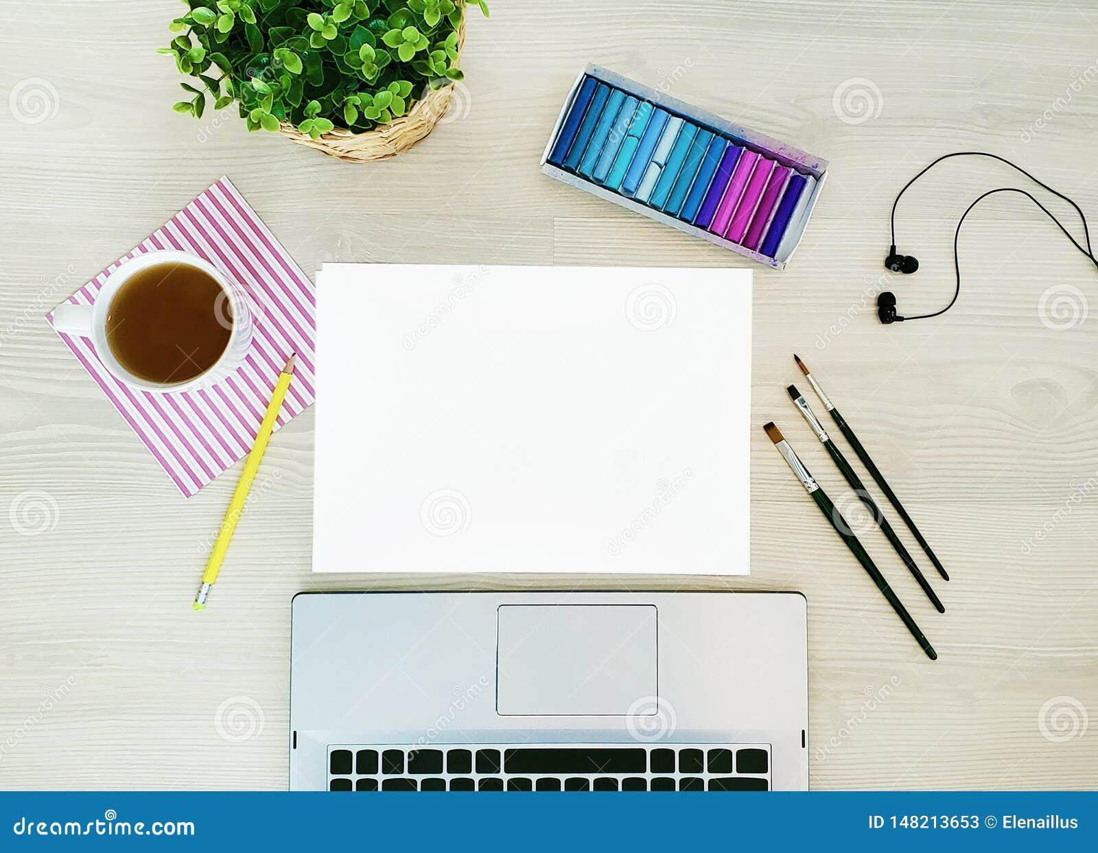 设计师,艺术家工作场所 创造性,时髦,艺术性的嘲笑与纸,咖啡、笔记本或者键盘,耳机,一支黄色铅笔