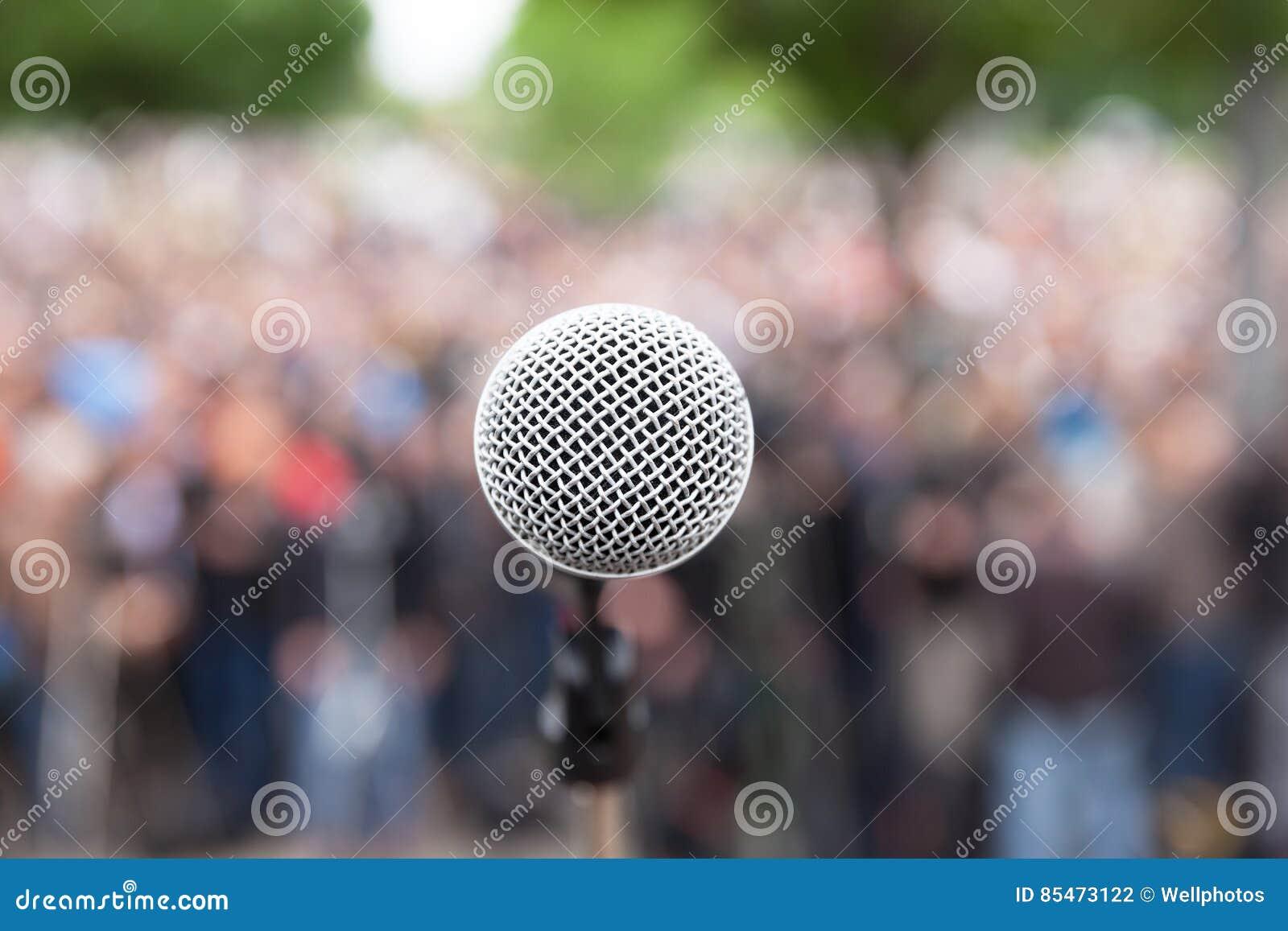 话筒在反对被弄脏的人群的焦点 政治集会