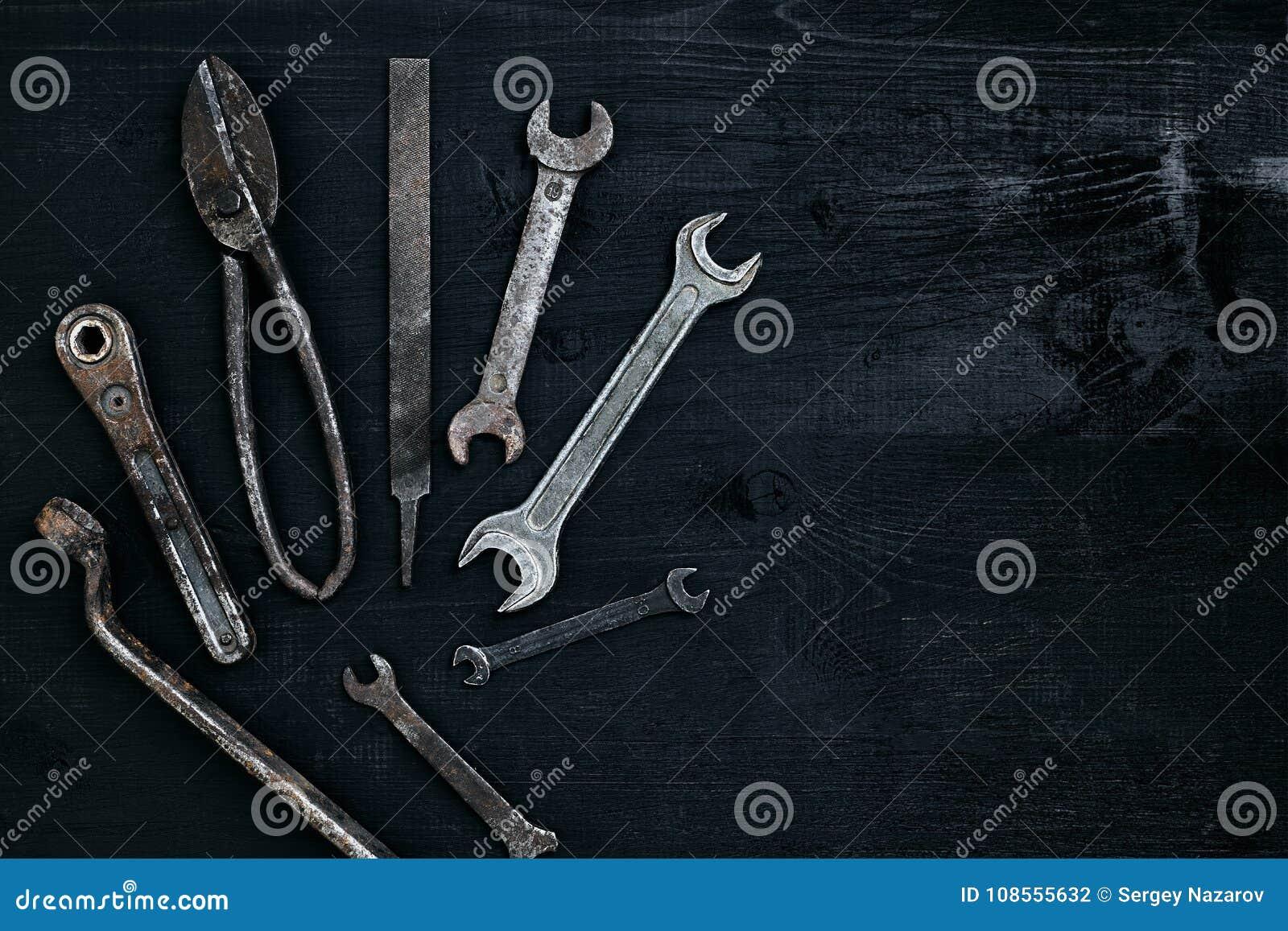 说谎在一张黑木桌上的老,生锈的工具 锤子,凿子,金属剪,板钳