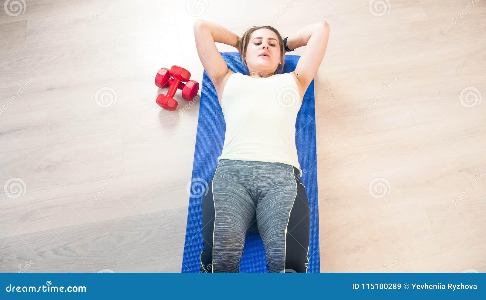 说谎在健身席子和做吸收仰卧起坐的美丽的少妇