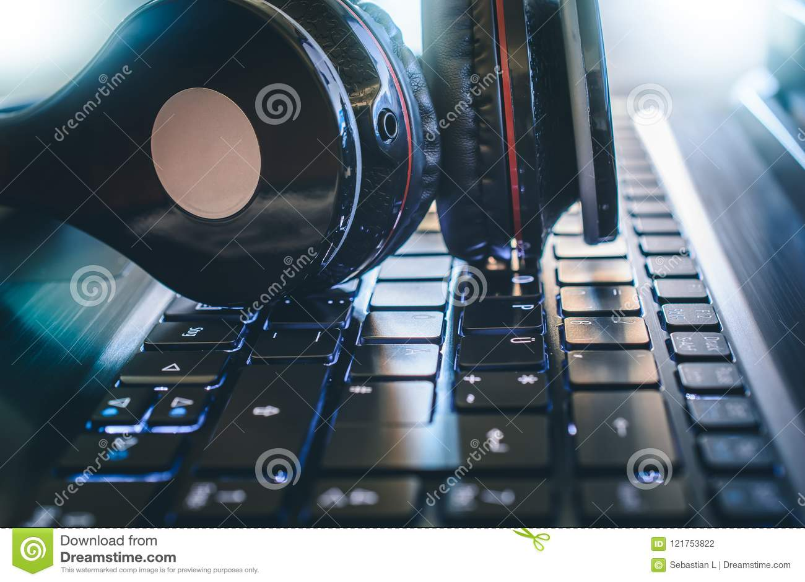 说谎在有明亮的光的一个键盘的黑无线赌博或节目播音员耳机在背景中