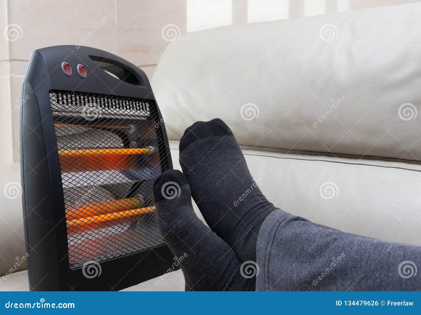 说谎在有电暖气的沙发的人在他的脚附近