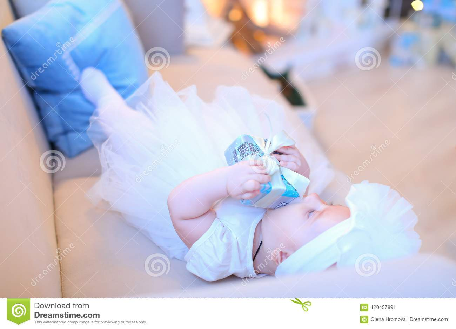 说谎在沙发和佩带的白色衣裳的小女性婴孩