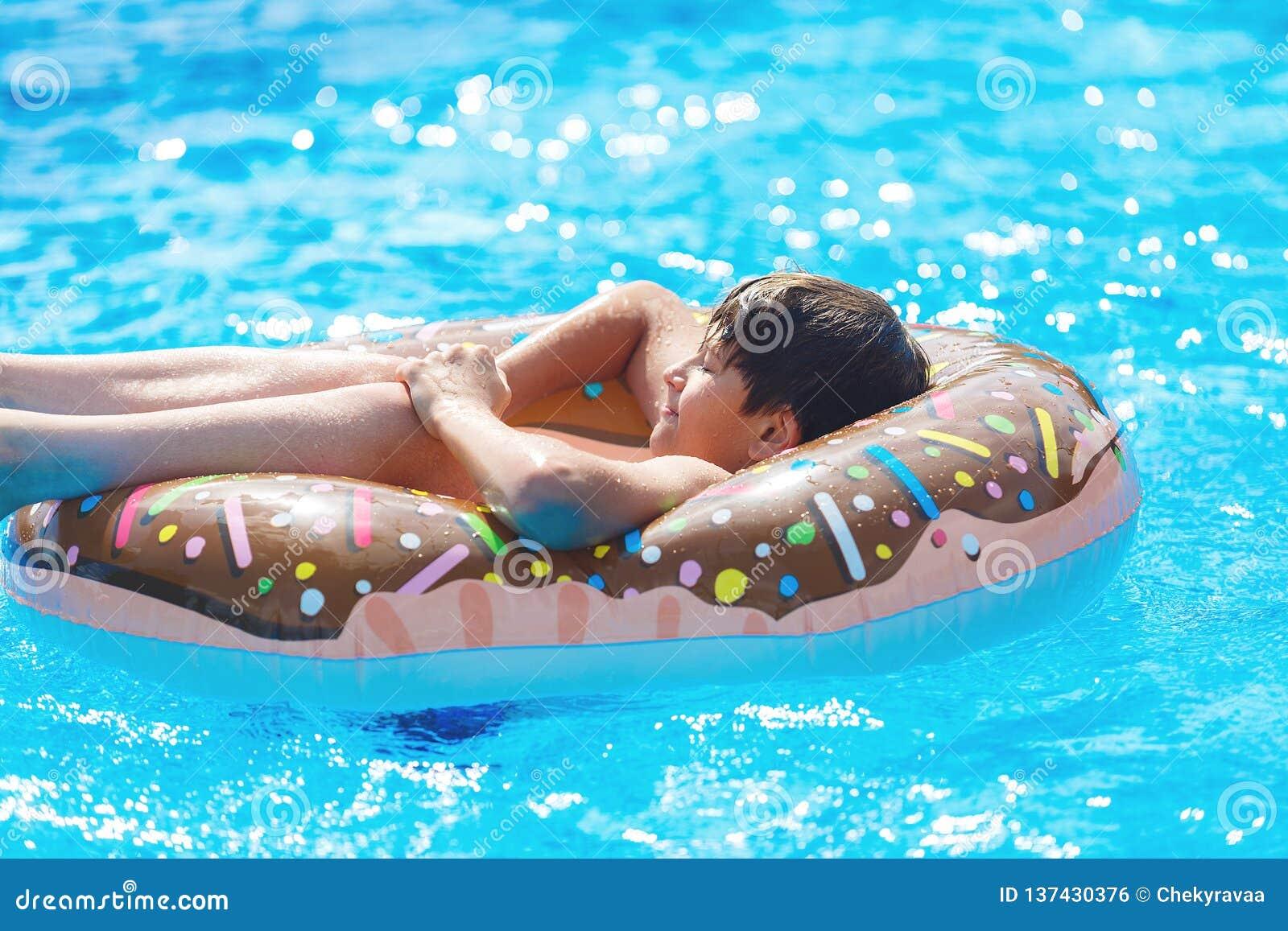 说谎在游泳场的一个可膨胀的多福饼圆环的愉快的逗人喜爱的小男孩少年 在水的活跃的游戏,假期,假日