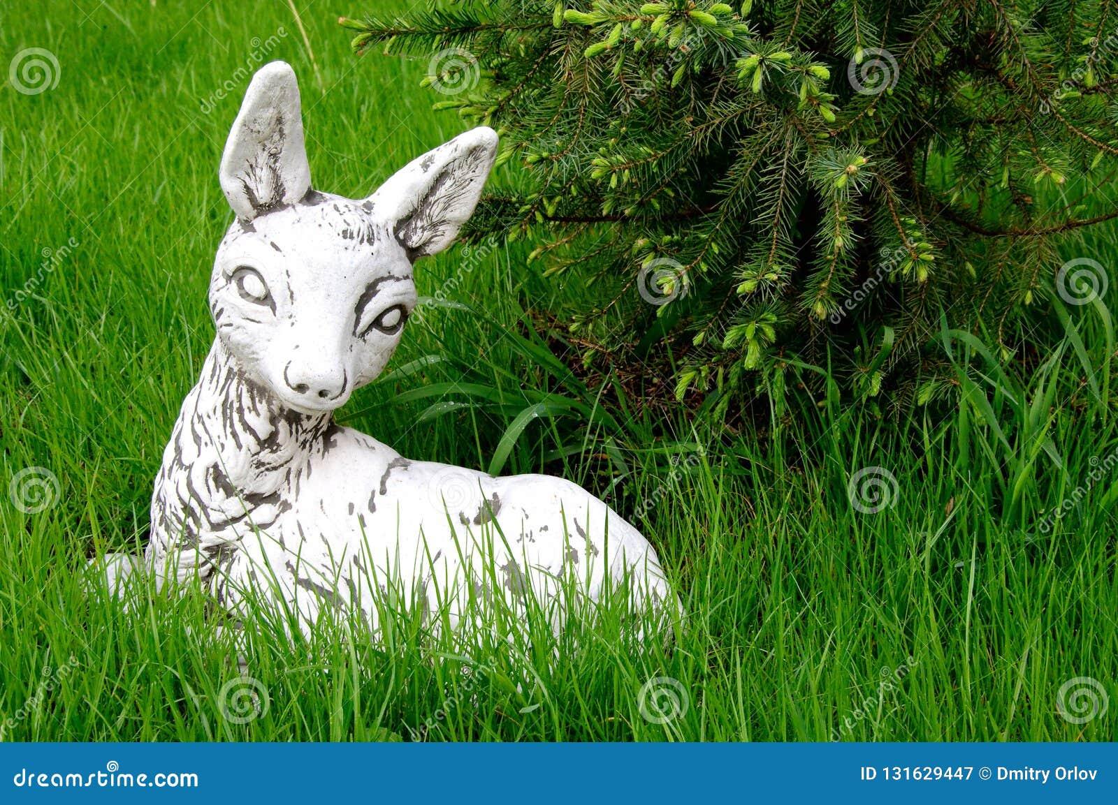 说谎在绿色草坪的石白色鹿bambi雕塑