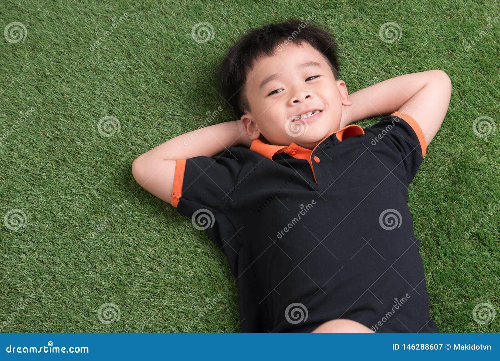 说谎在绿草的逗人喜爱的小男孩在公园