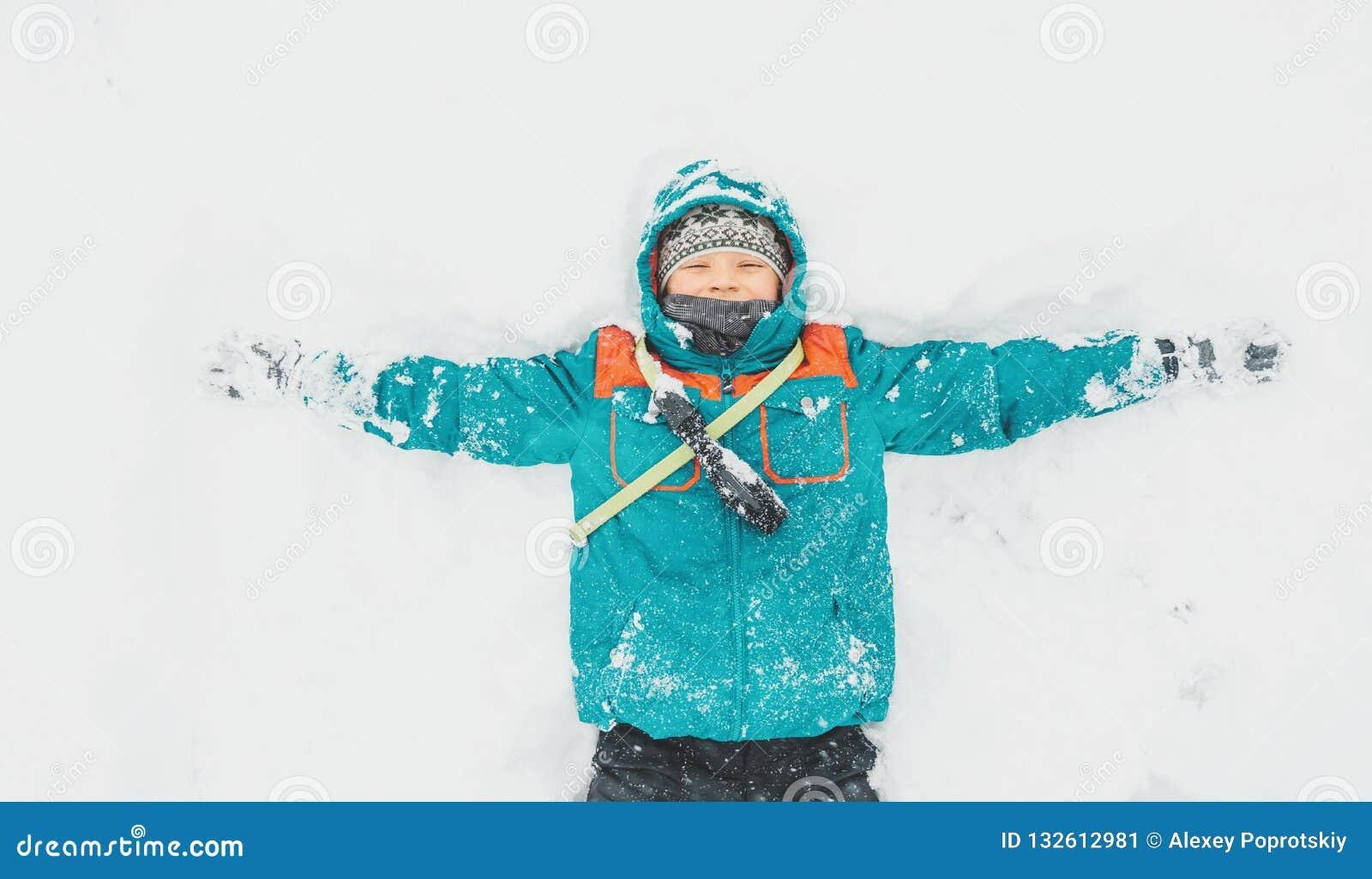 说谎在雪的愉快的男孩