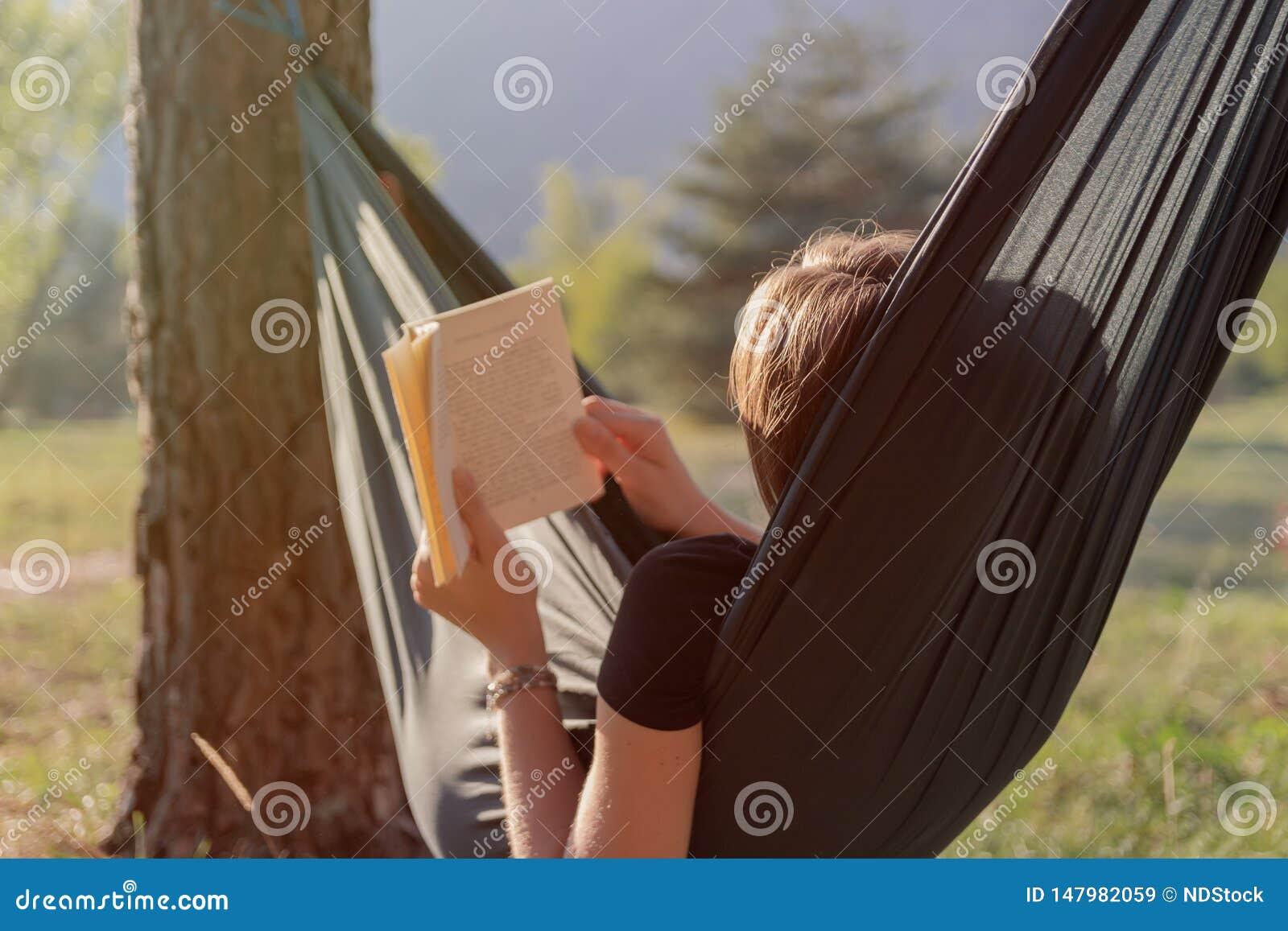 读书的年轻女人在吊床在日落期间