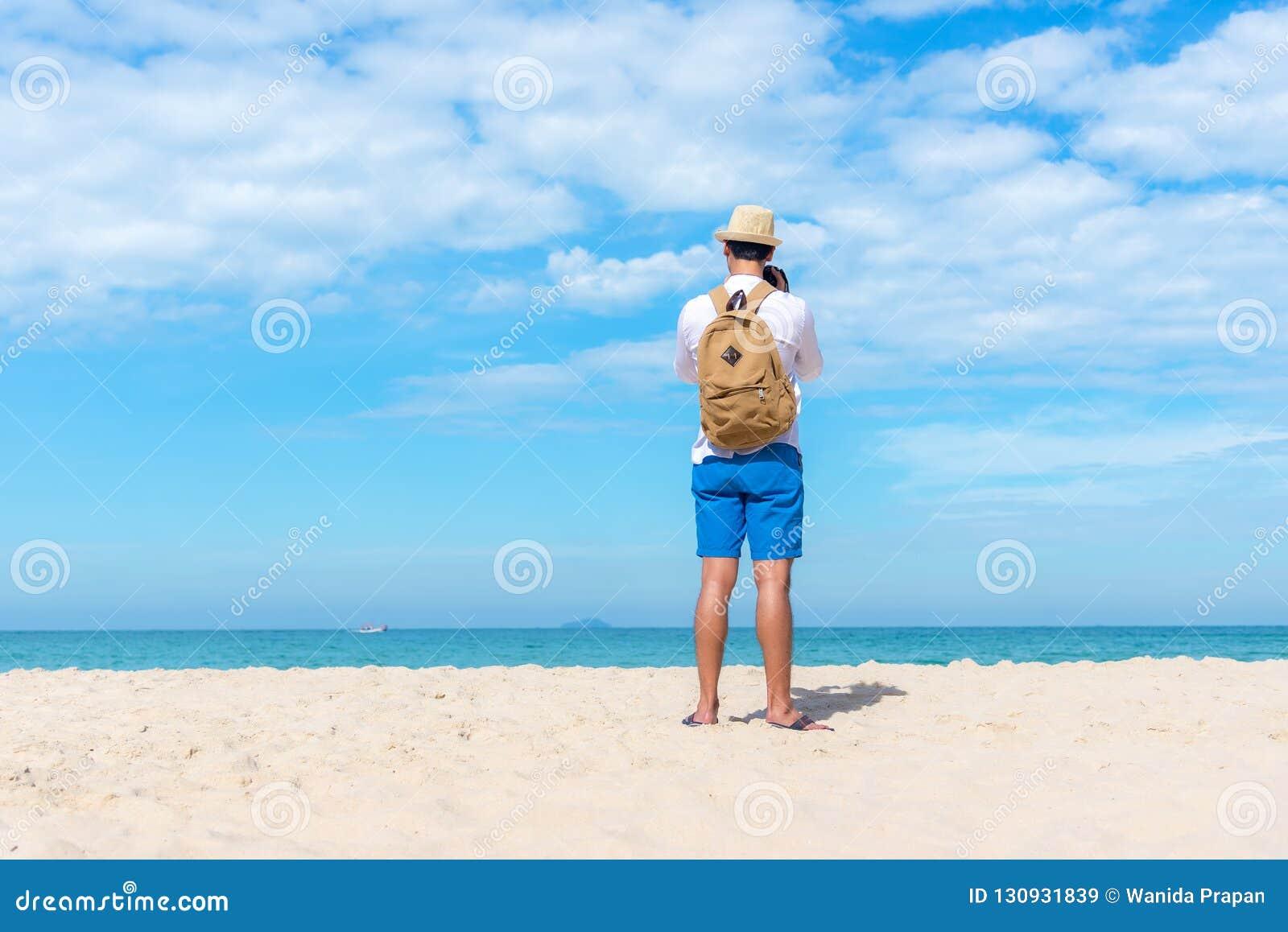 调遣结构树 拿着照相机为的愉快的微笑的白种人旅游亚裔年轻人在海滩拍照片登记