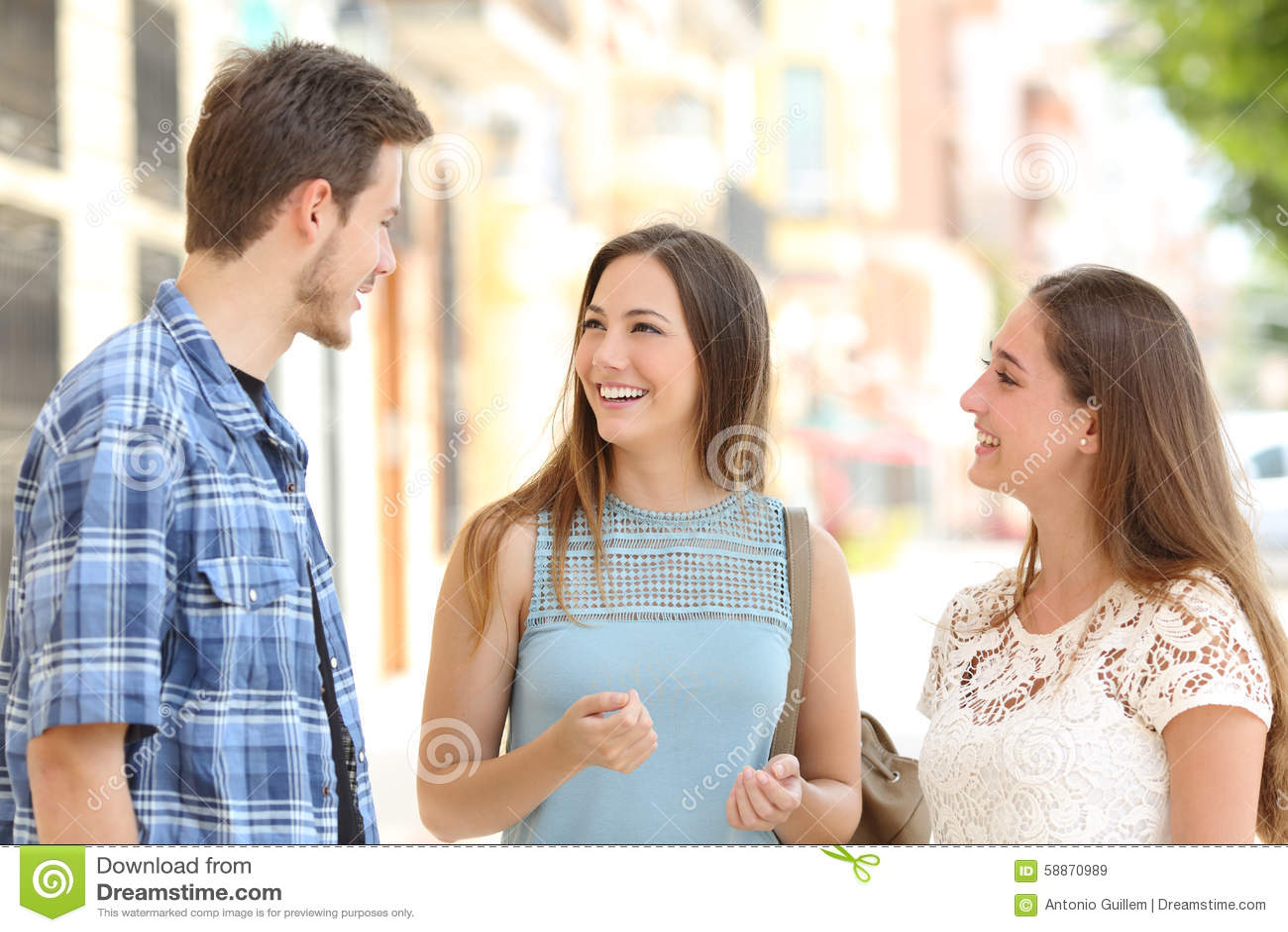 谈话三个的朋友采取在街道上的一次交谈