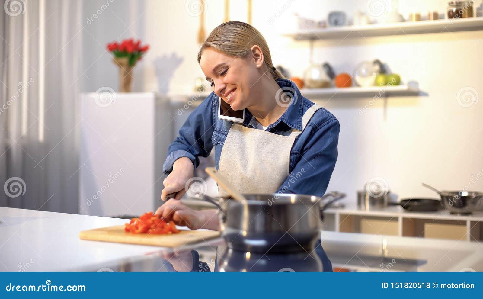 谈话在电话和准备西红柿酱,容易的食物食谱的年轻女人