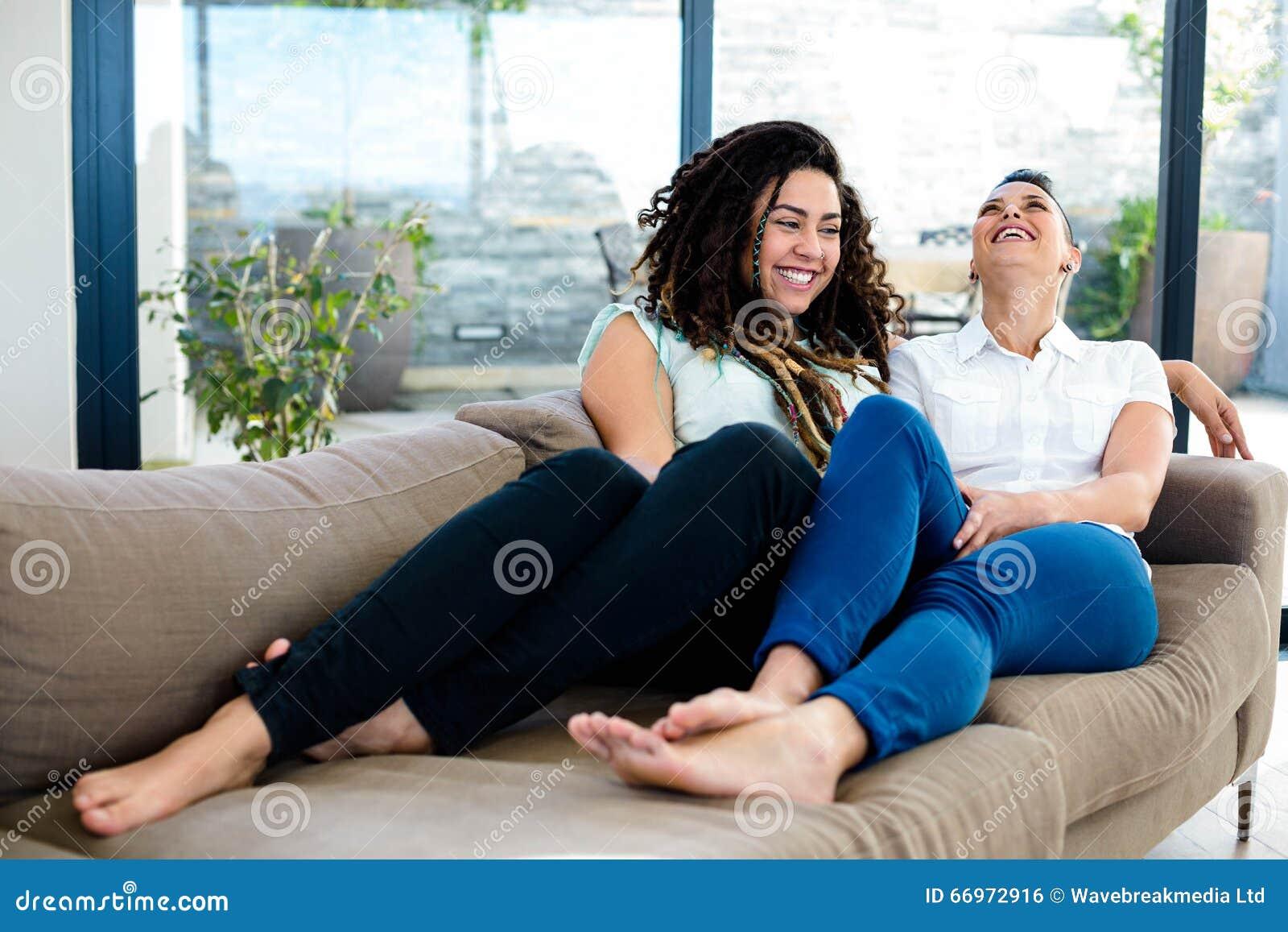 女同性恋的夫妇互相微笑和谈话在客厅.