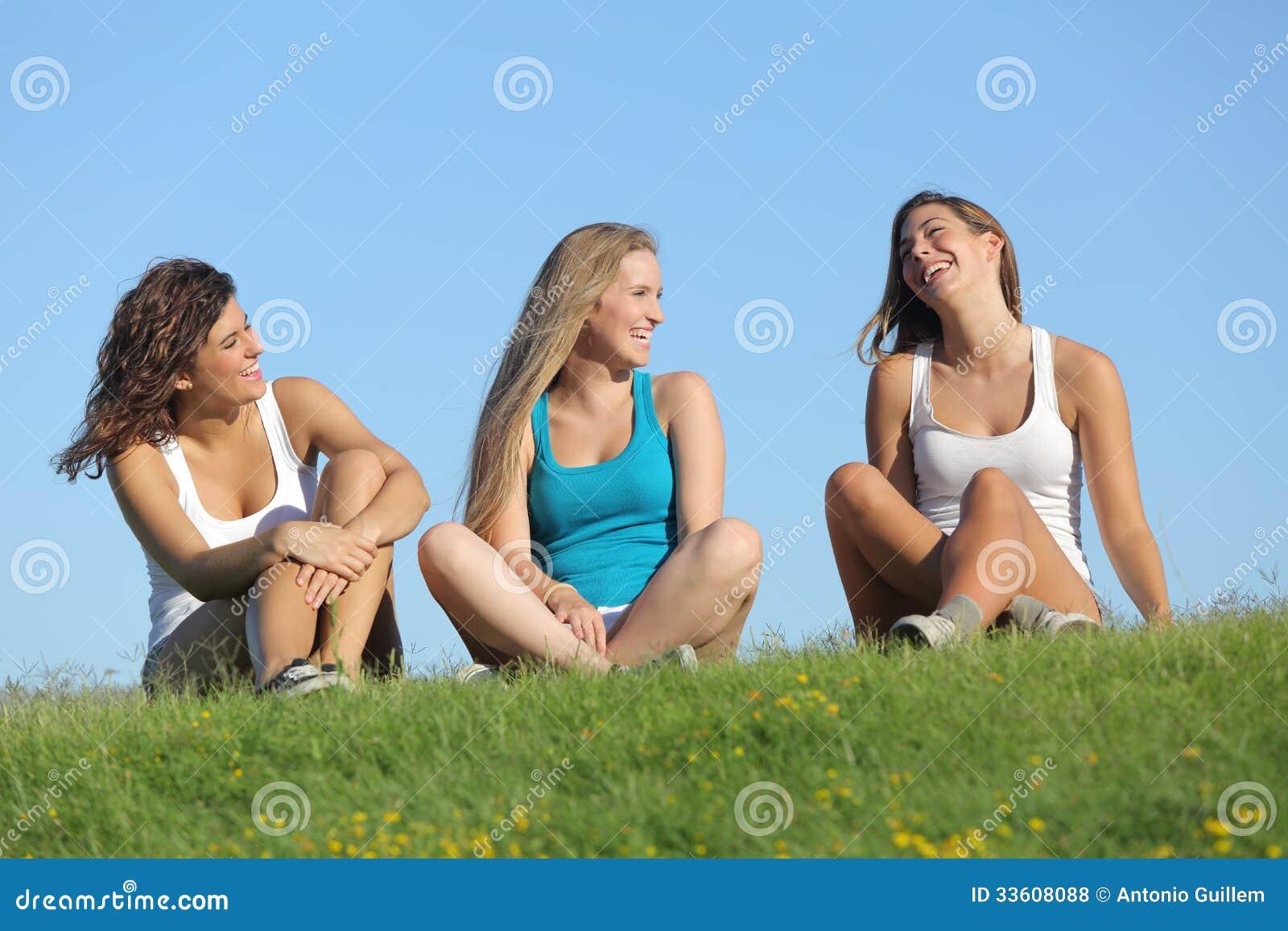 谈话小组三个少年的女孩笑和室外