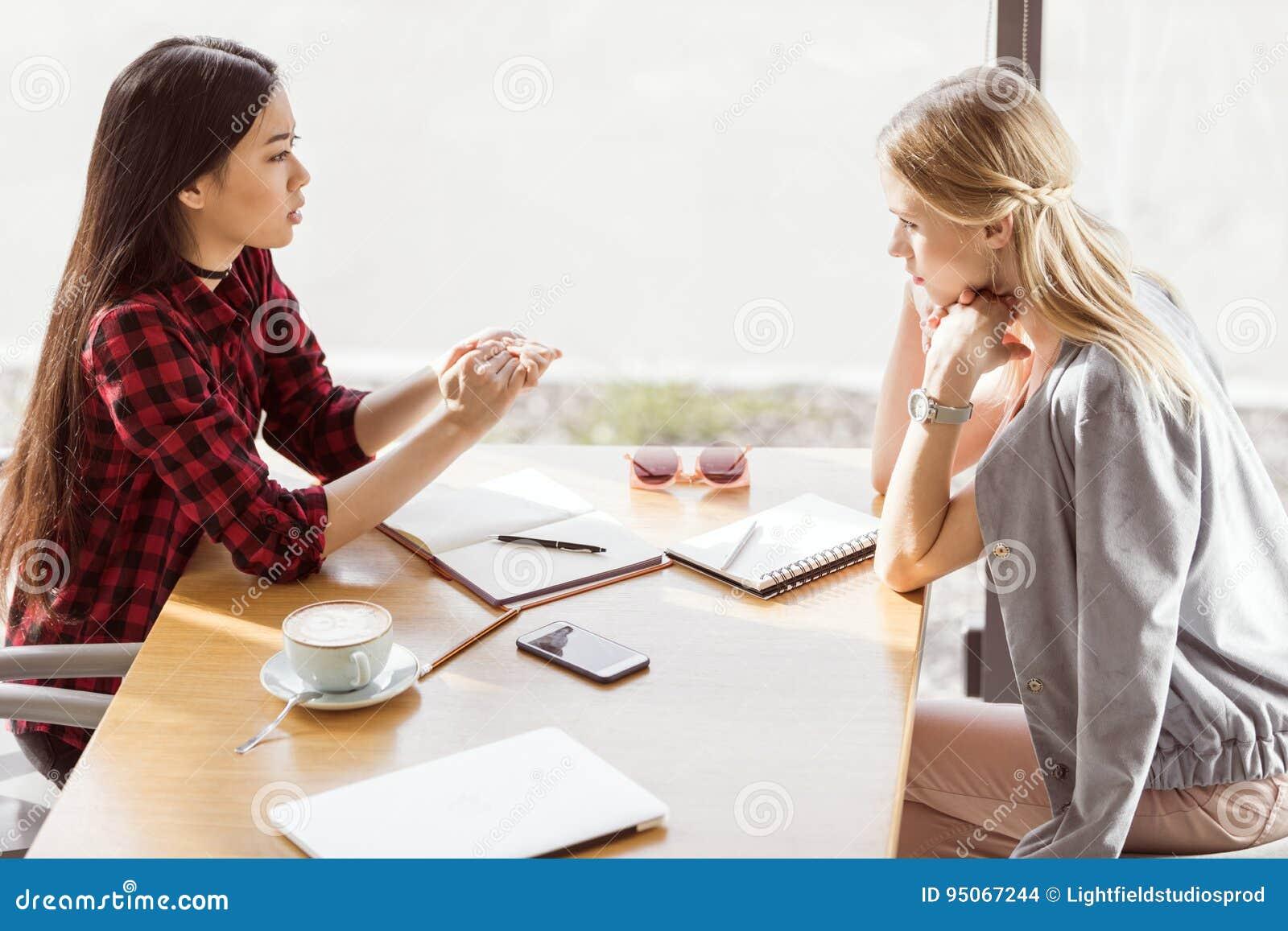 谈话的少妇,当开工作午餐会议在咖啡馆时