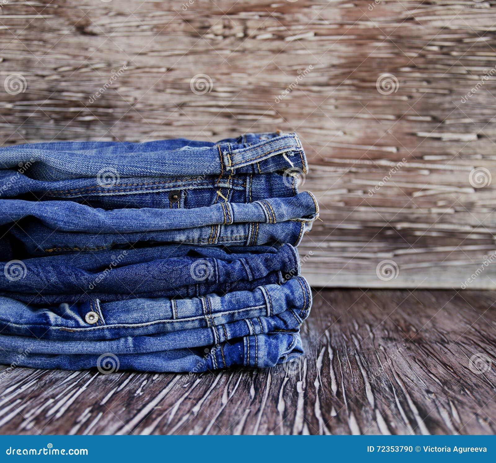 说谎在一张木桌上的堆牛仔裤