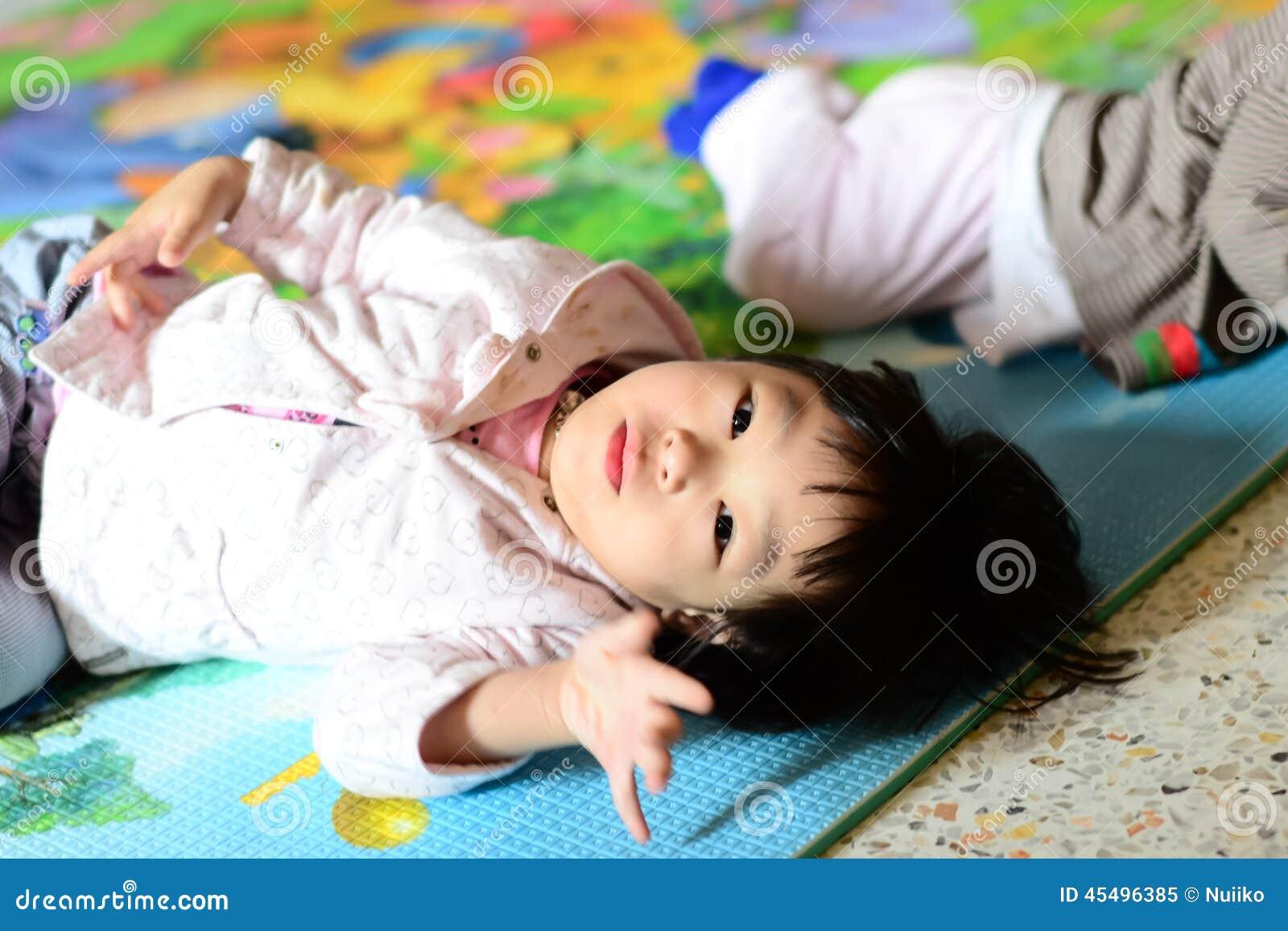 说谎在地板上的逗人喜爱的亚裔女孩