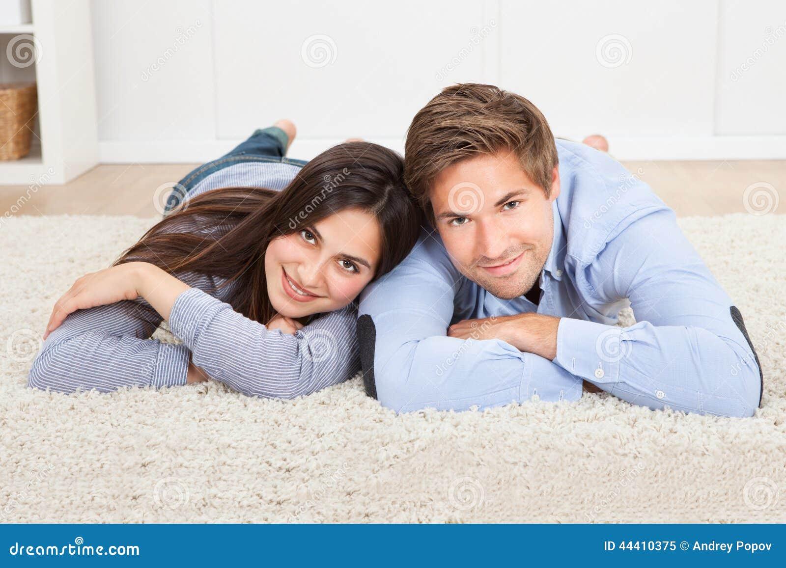 说谎在地毯的愉快的夫妇在客厅