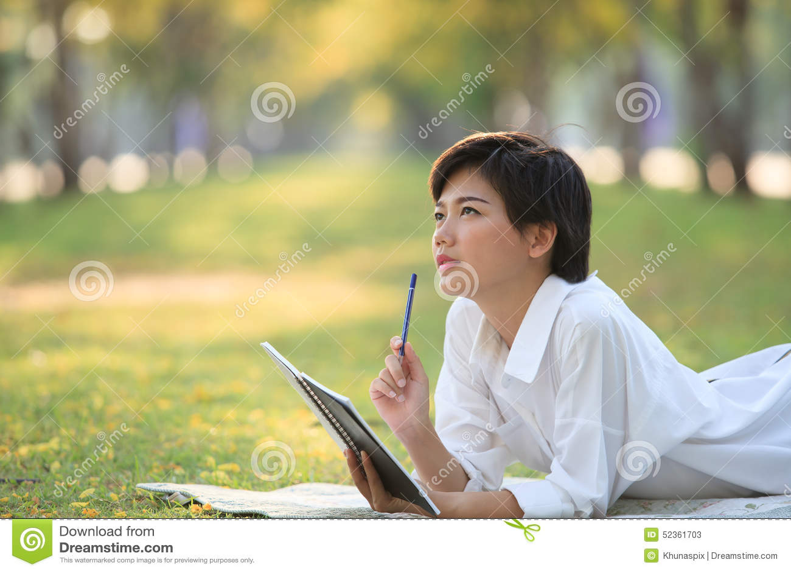 说谎在有铅笔和笔记本的绿草公园的少妇