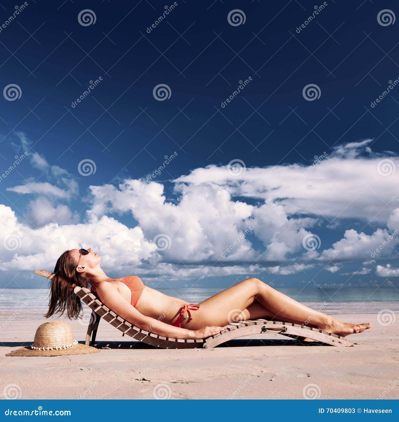 说谎在海滩的比基尼泳装的妇女在塞舌尔群岛