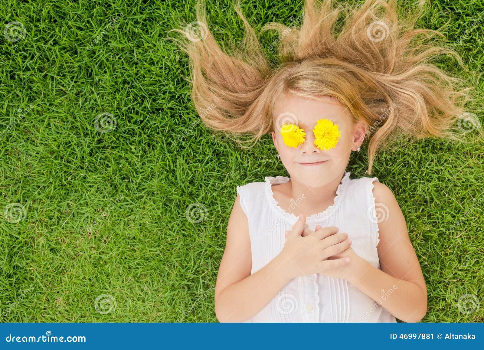 说谎在草的一个愉快的小女孩