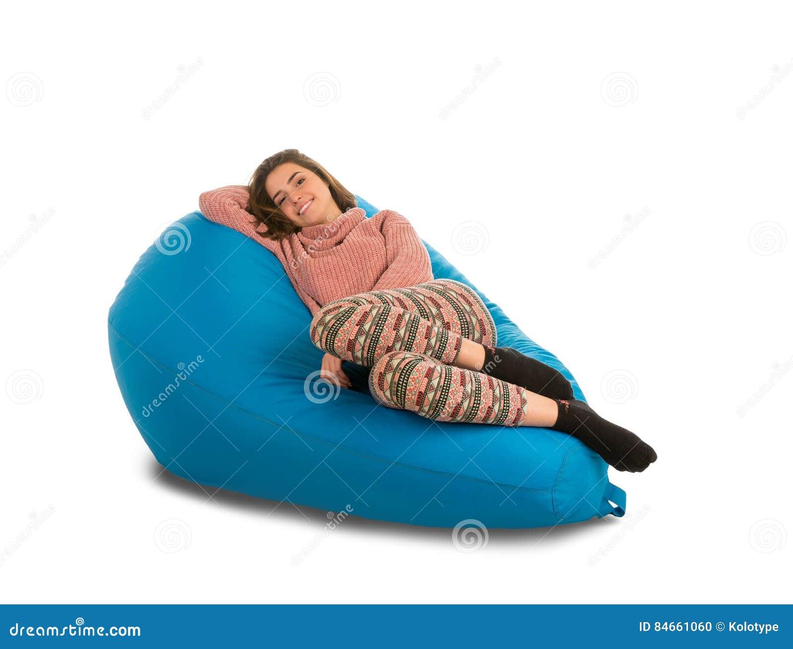 说谎在蓝色装豆子小布袋沙发的美丽的少妇