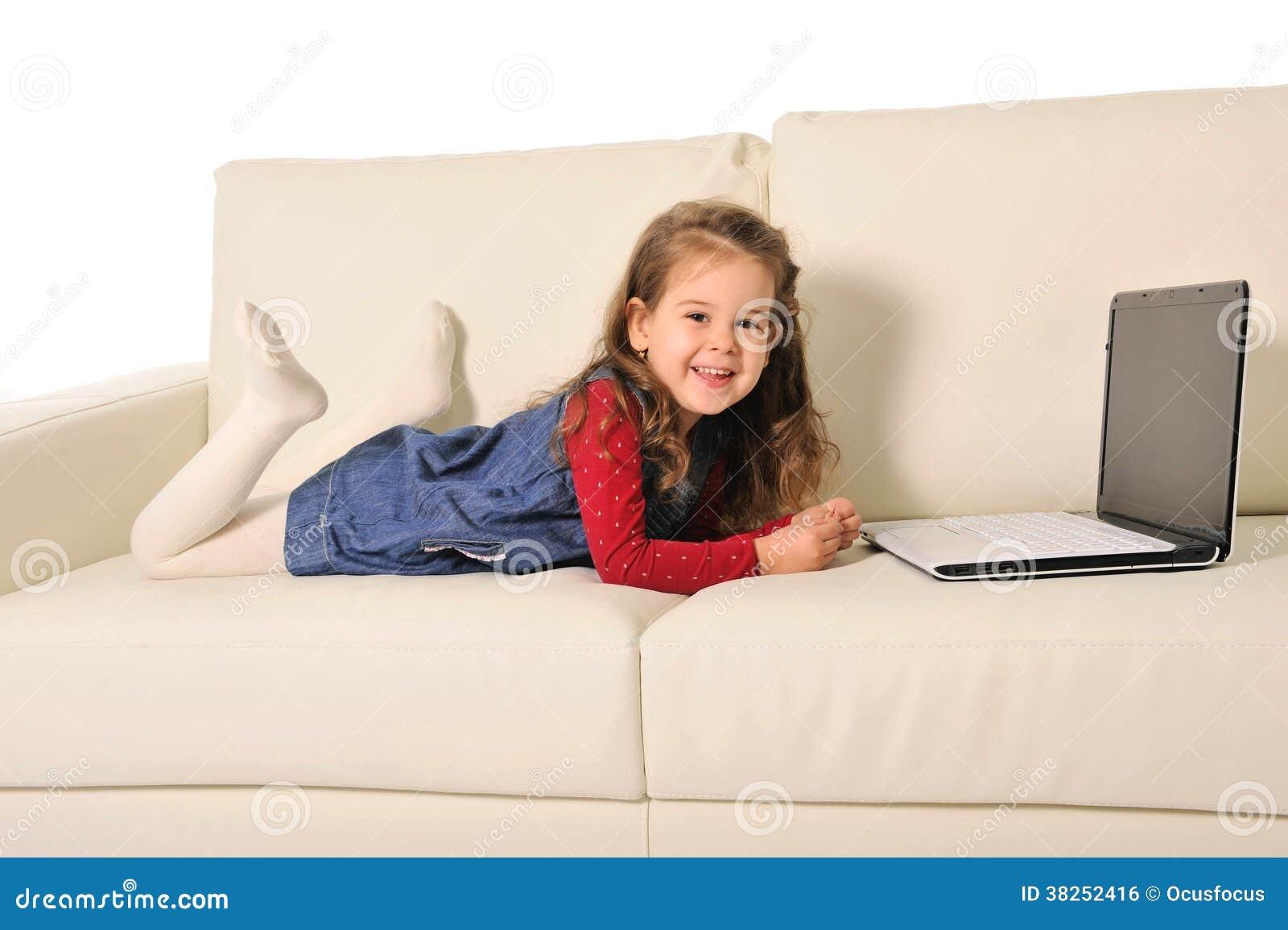 说谎在长沙发的愉快的小女孩使用与计算机