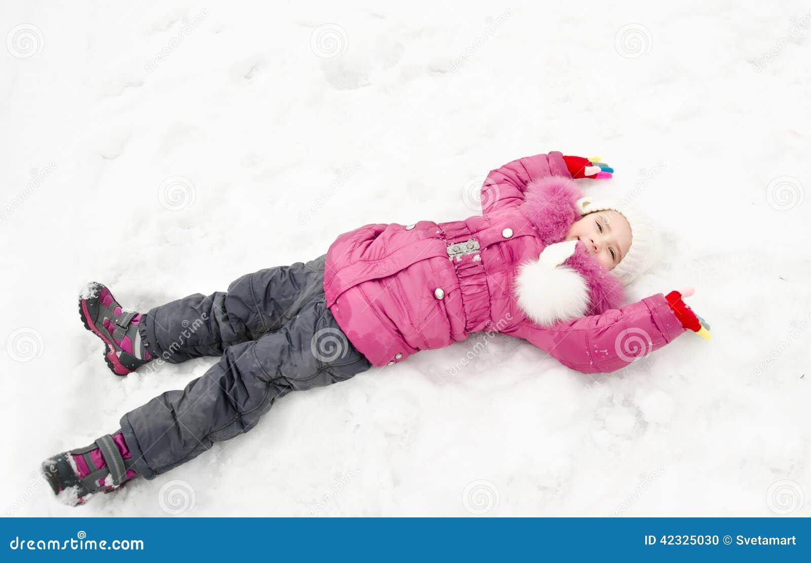 说谎在雪的逗人喜爱的微笑的小女孩在冬日