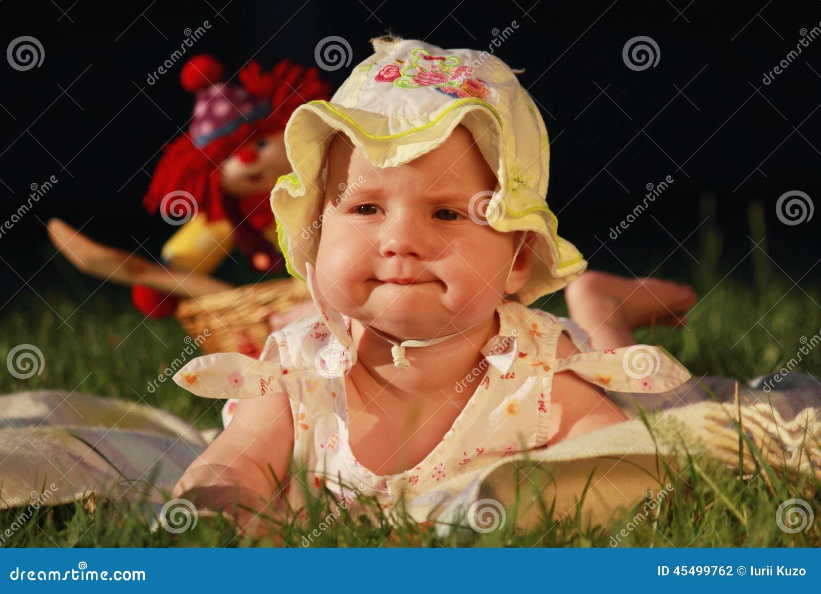 说谎在绿色草坪的可爱的女婴
