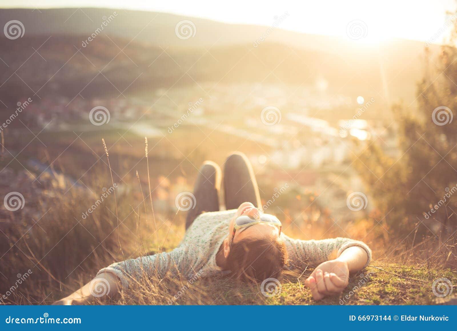 说谎在绿草草甸的无忧无虑的愉快的妇女在山享用在她的面孔的边缘峭壁顶部太阳 享受自然日落