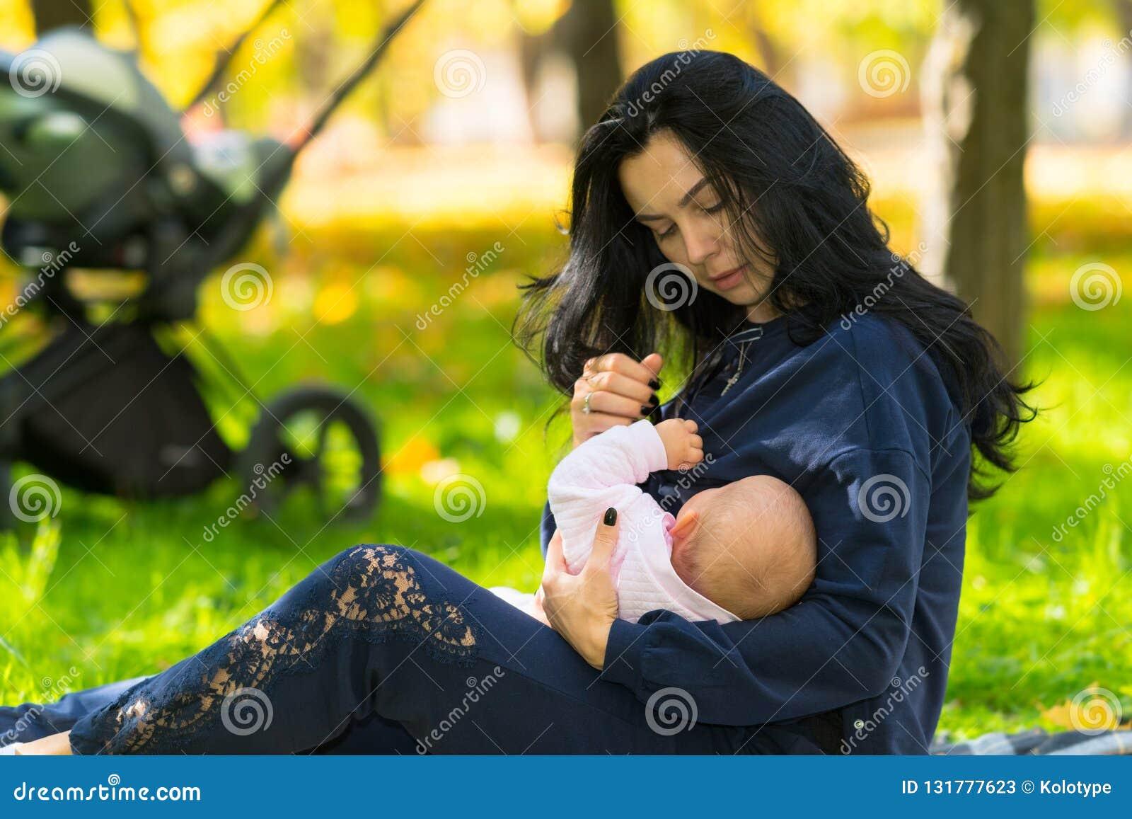 谨慎地哺乳婴孩的母亲户外