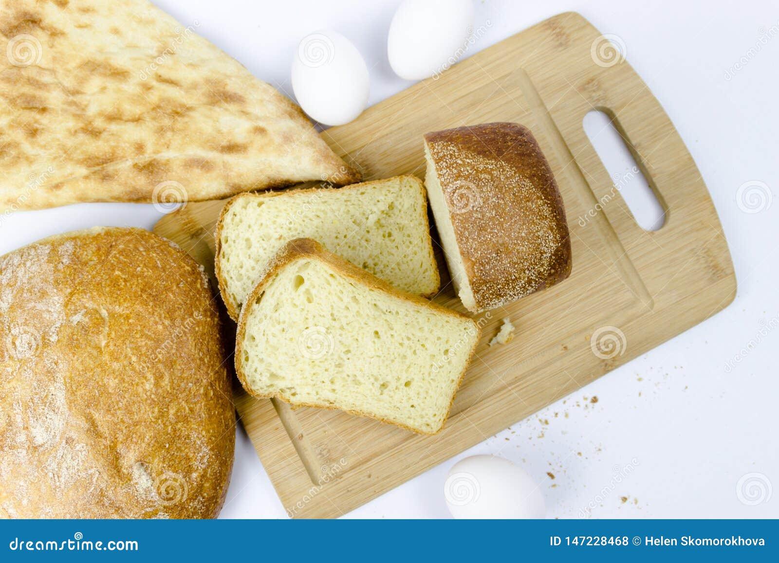 谷物面包店不同形式的分类顶视图:面包,新月形面包,在白色隔绝的小圆面包woodden背景