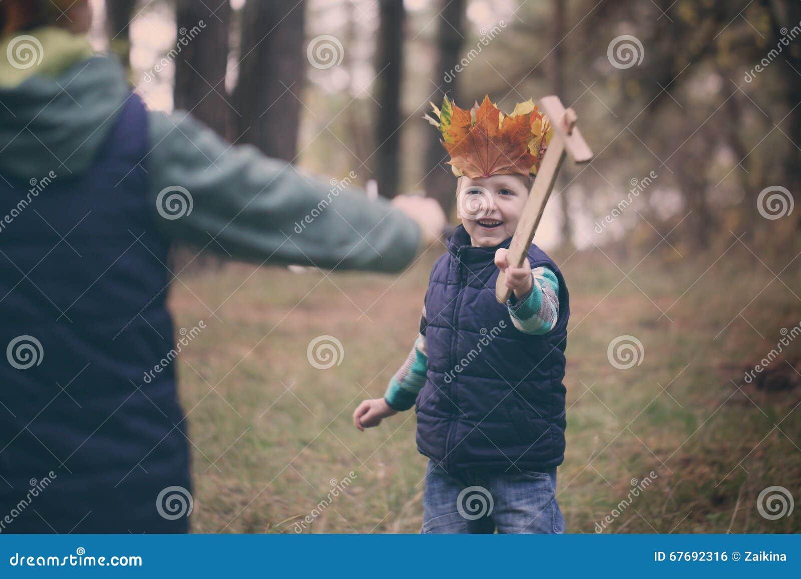 画象小男孩在一个森林里在秋天天 男孩有一个冠
