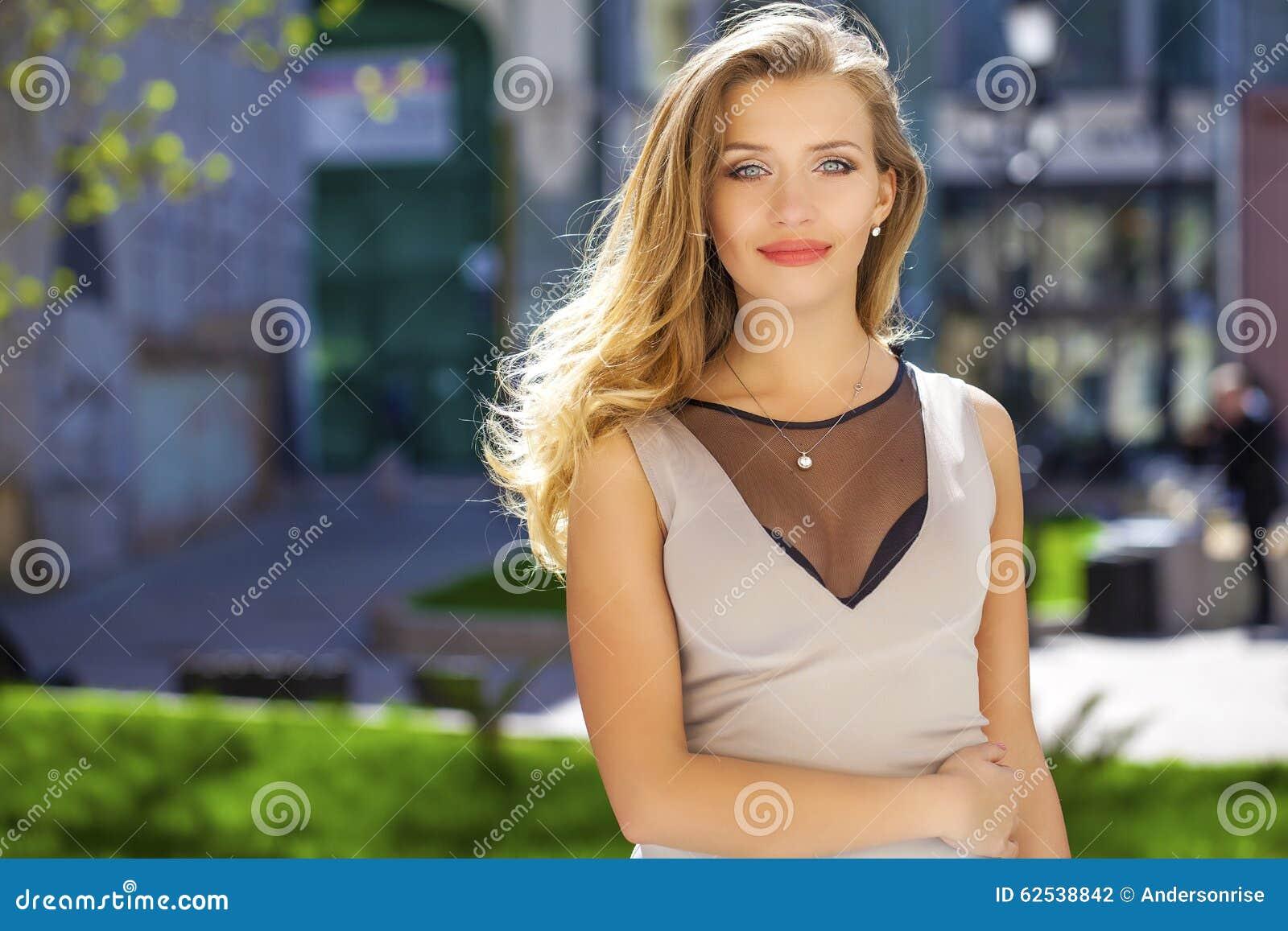 画象接近年轻美丽的白肤金发的妇女,背景的