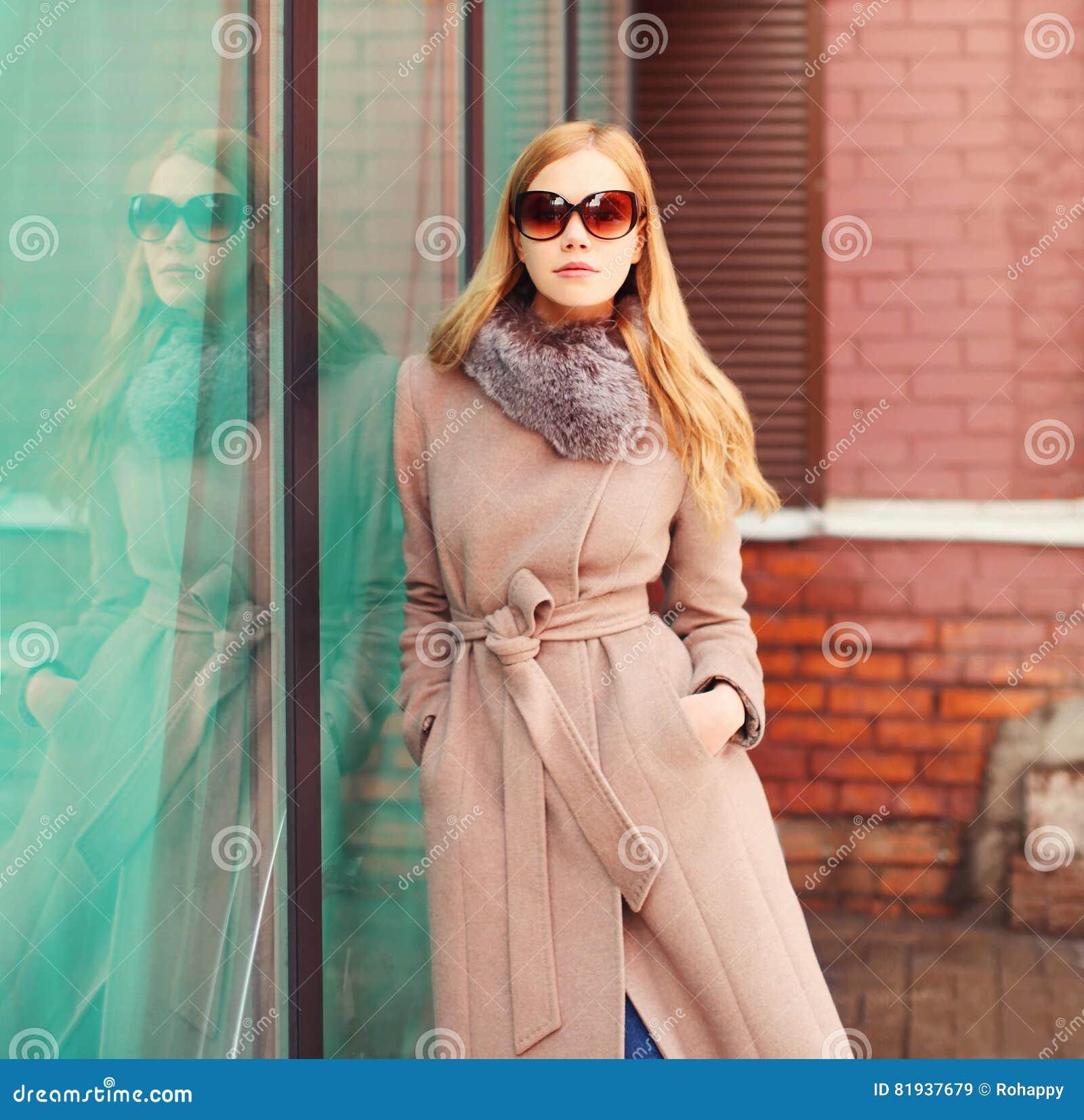 画象美丽的典雅的白肤金发的妇女佩带的外套夹克和太阳镜在城市