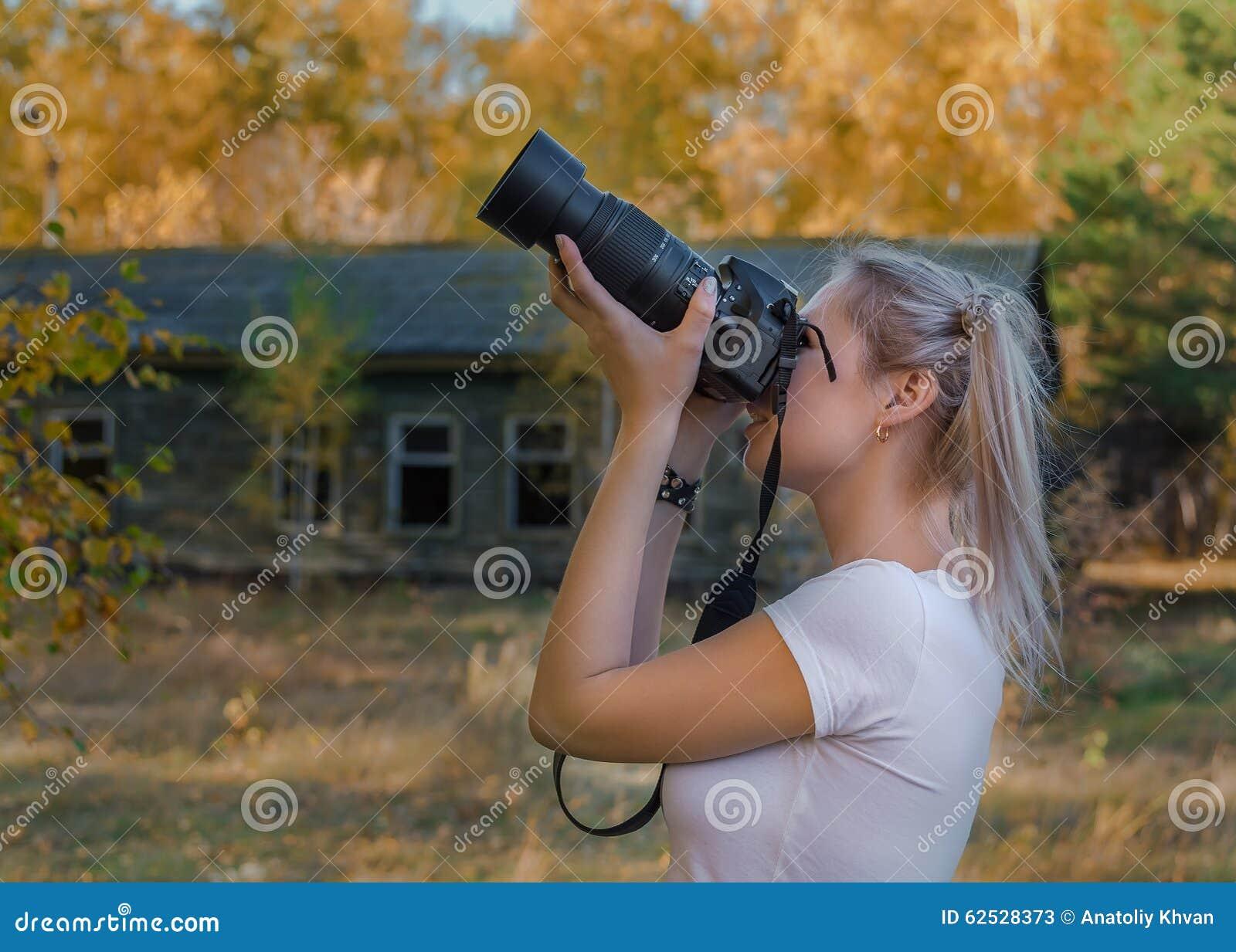 画象年轻迷人的妇女照相机微笑的backgroynd秋天公园
