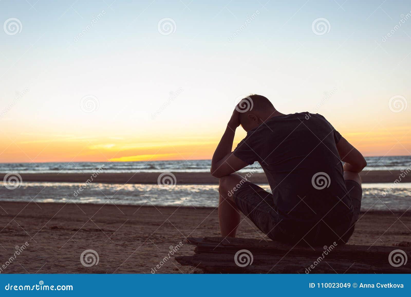 负担由未看见的忧虑 哀伤的孤独的人坐海滩