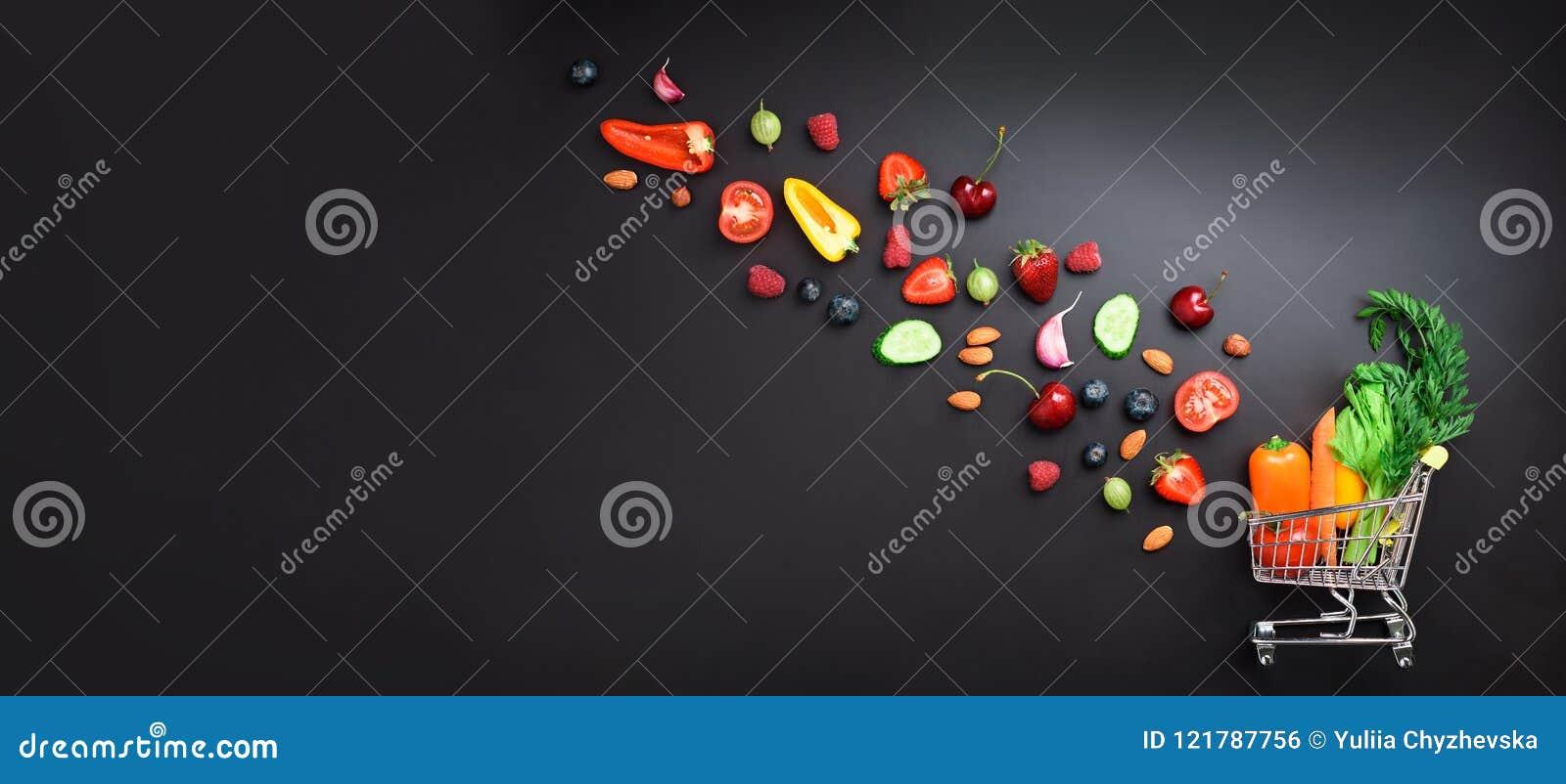 购物台车用新鲜的有机蔬菜、水果和莓果填装了在黑黑板 顶视图 素食主义者