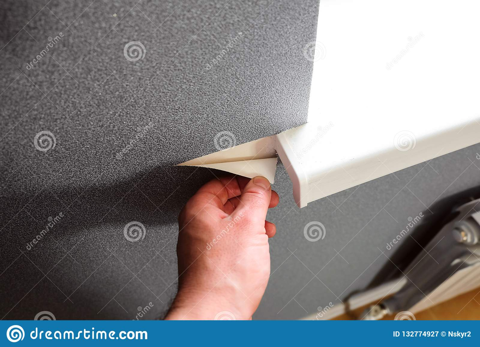 贴墙纸在公寓的明亮的窗口开头附近的灰色