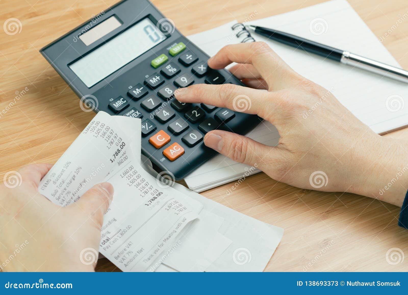 费用和费用演算或者票据付款概念,手在计算器上把手指和黑笔放在纸笔记薄