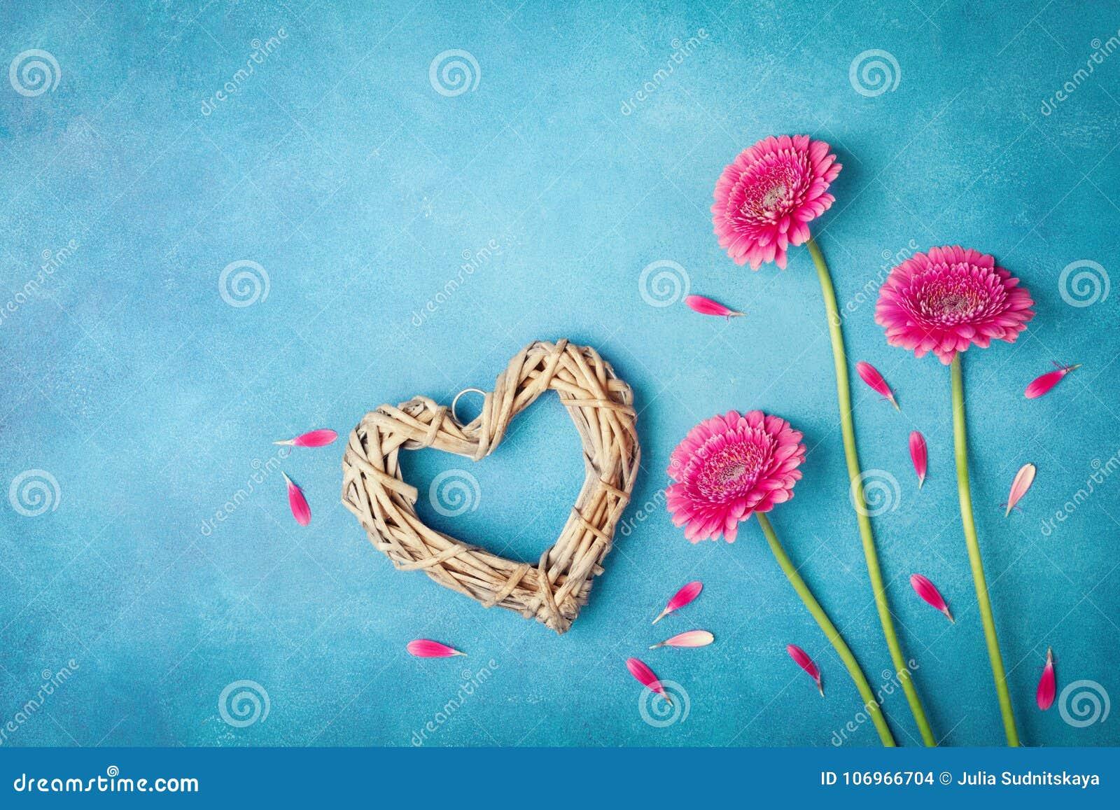 贺卡为妇女或母亲节 与桃红色花、心脏和瓣的春天背景 平的位置样式 顶视图