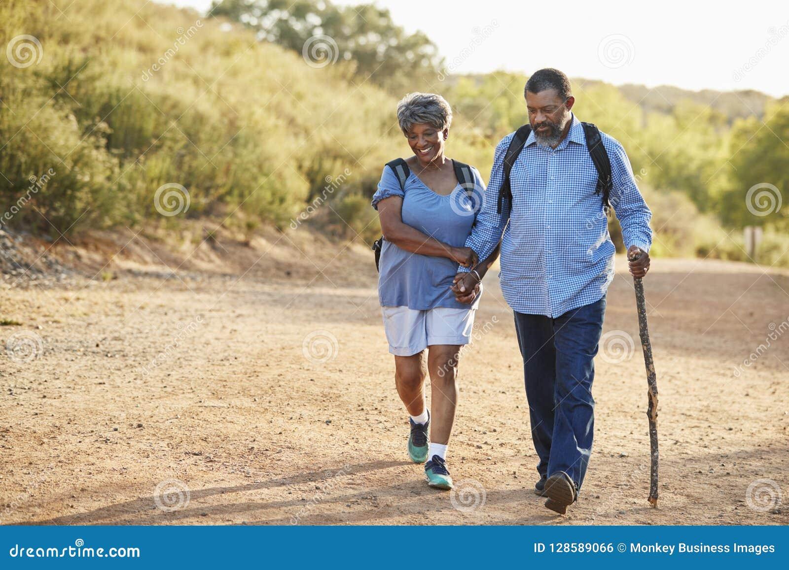 资深一起远足在乡下的夫妇佩带的背包
