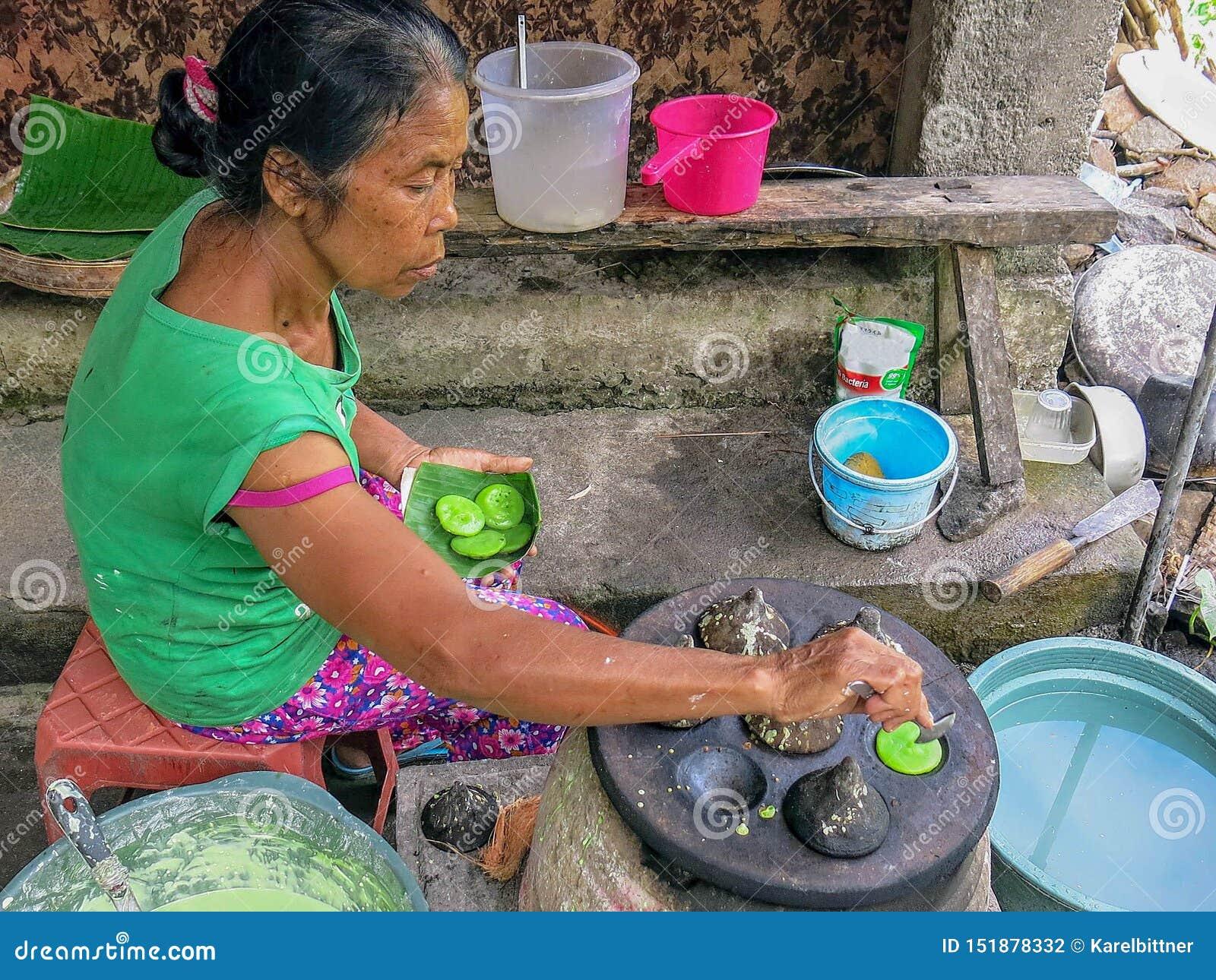资深印度尼西亚妇女准备传统甜盘 由被烘烤以石形式的面团做的一个非常鲜美点心 Primiti