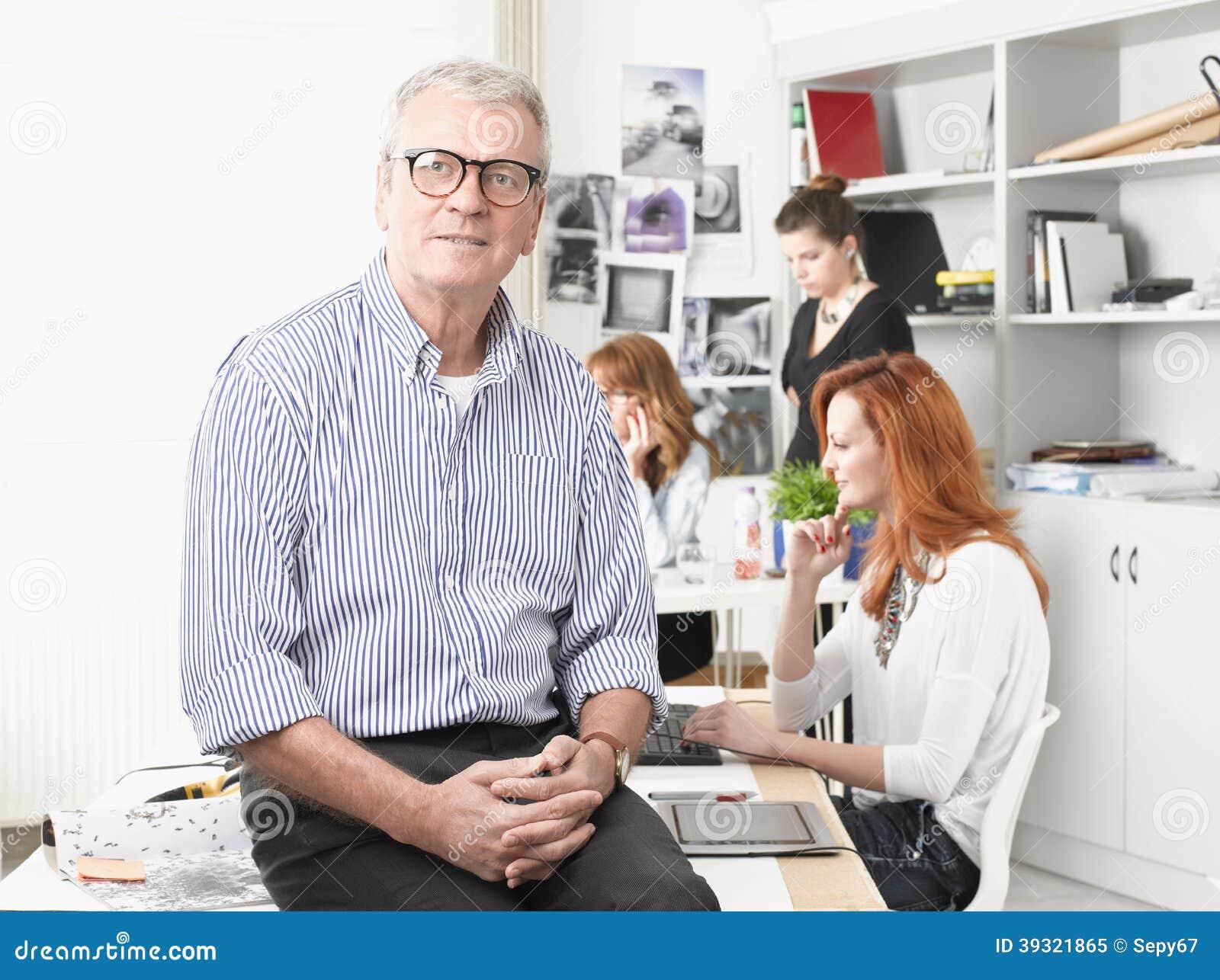 坐书桌和工作在演播室的资深图表设计师 3d商业查出的小的白色.图片