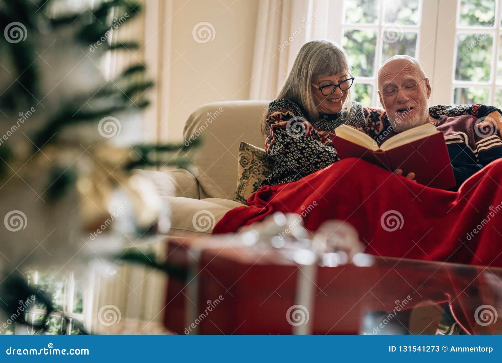 资深夫妇坐享用的沙发读与一个礼物盒的一本书在前景 微笑的夫妇消费时间一起
