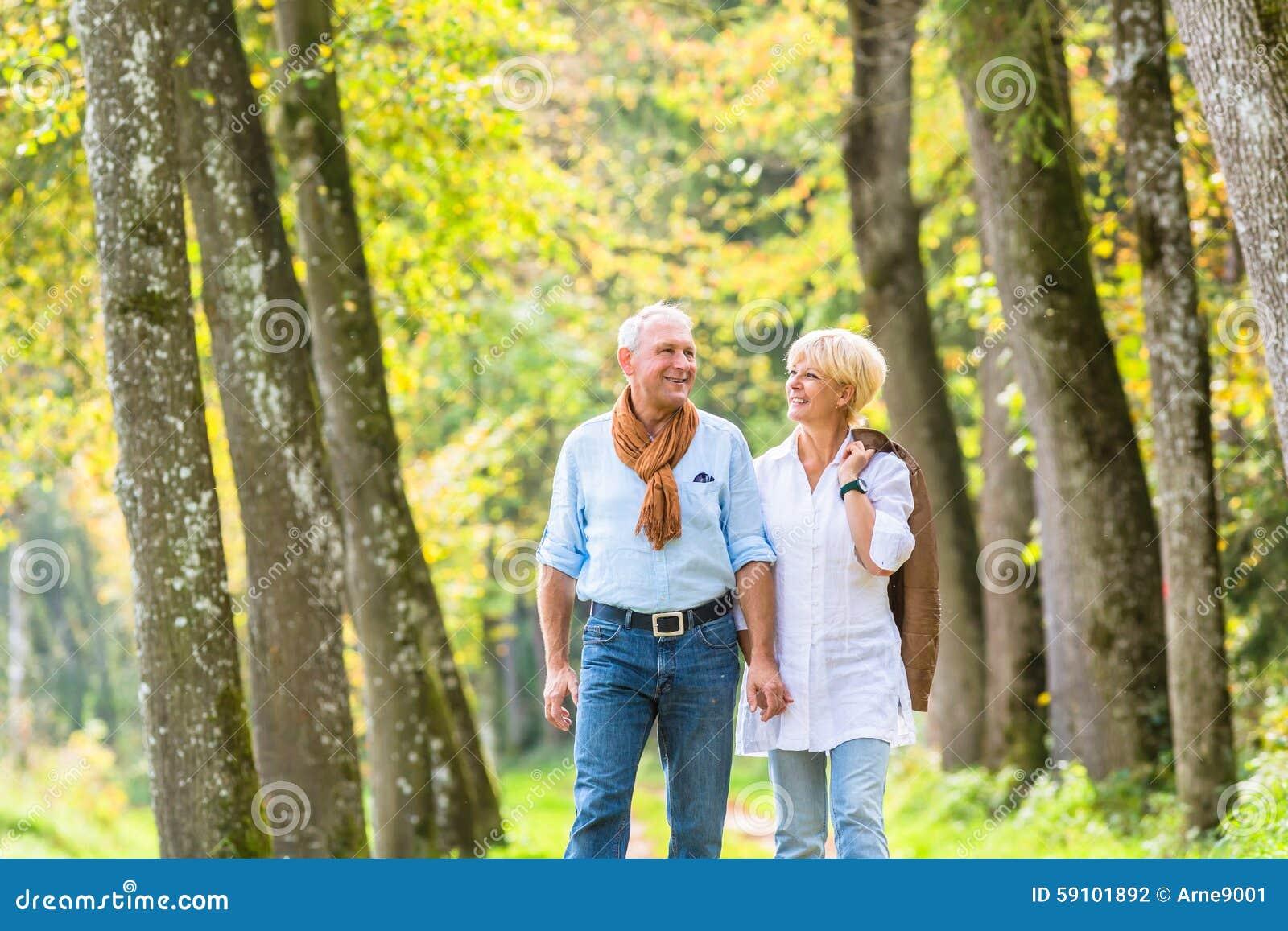 资深夫妇有休闲步行在森林