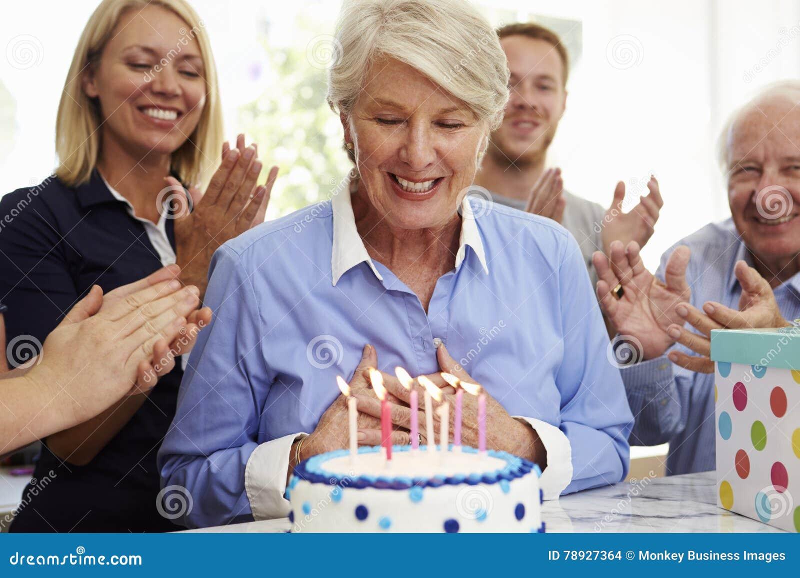 资深妇女吹灭生日蛋糕蜡烛在家庭党