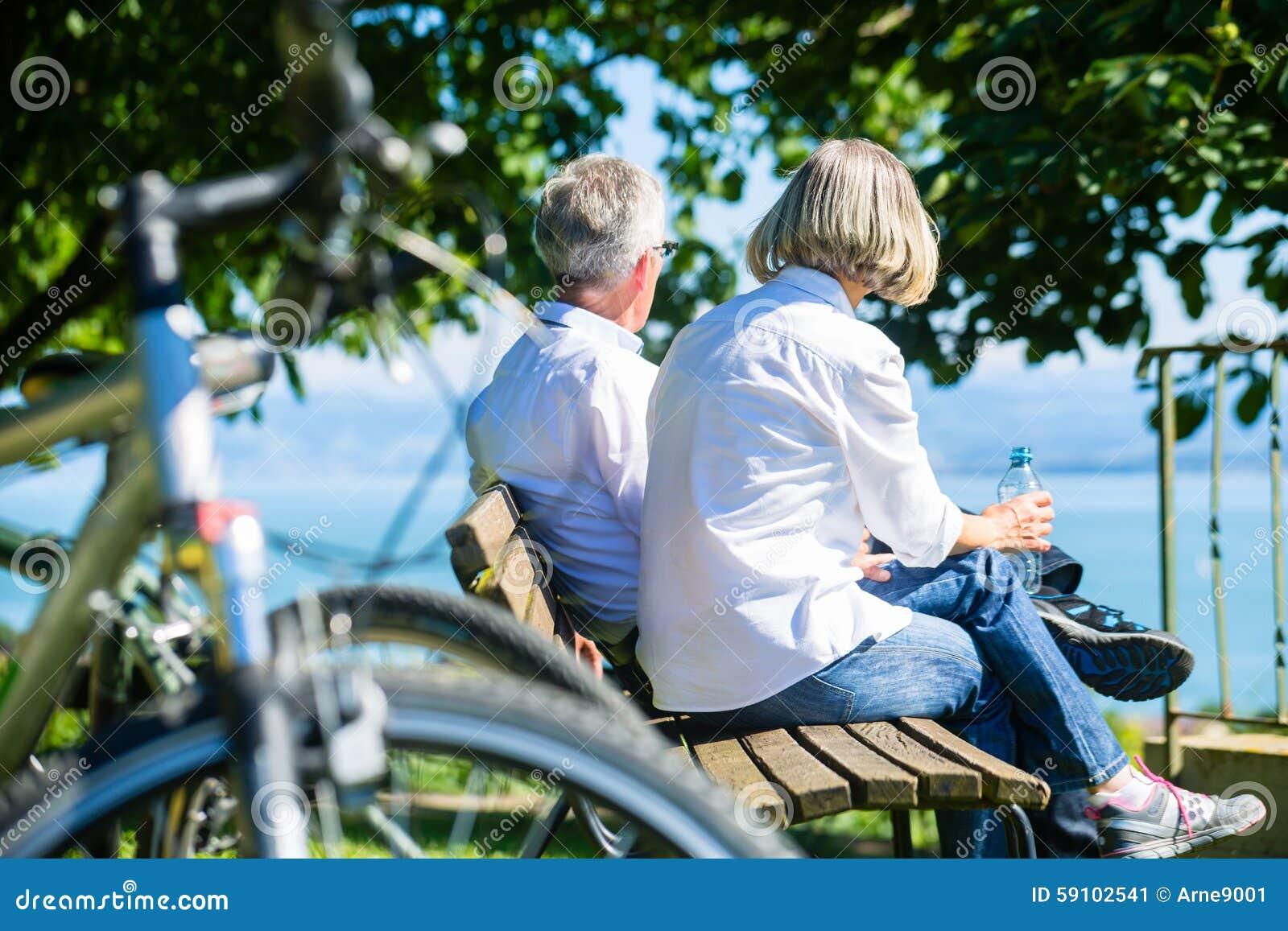 资深妇女和人休息自行车旅行的