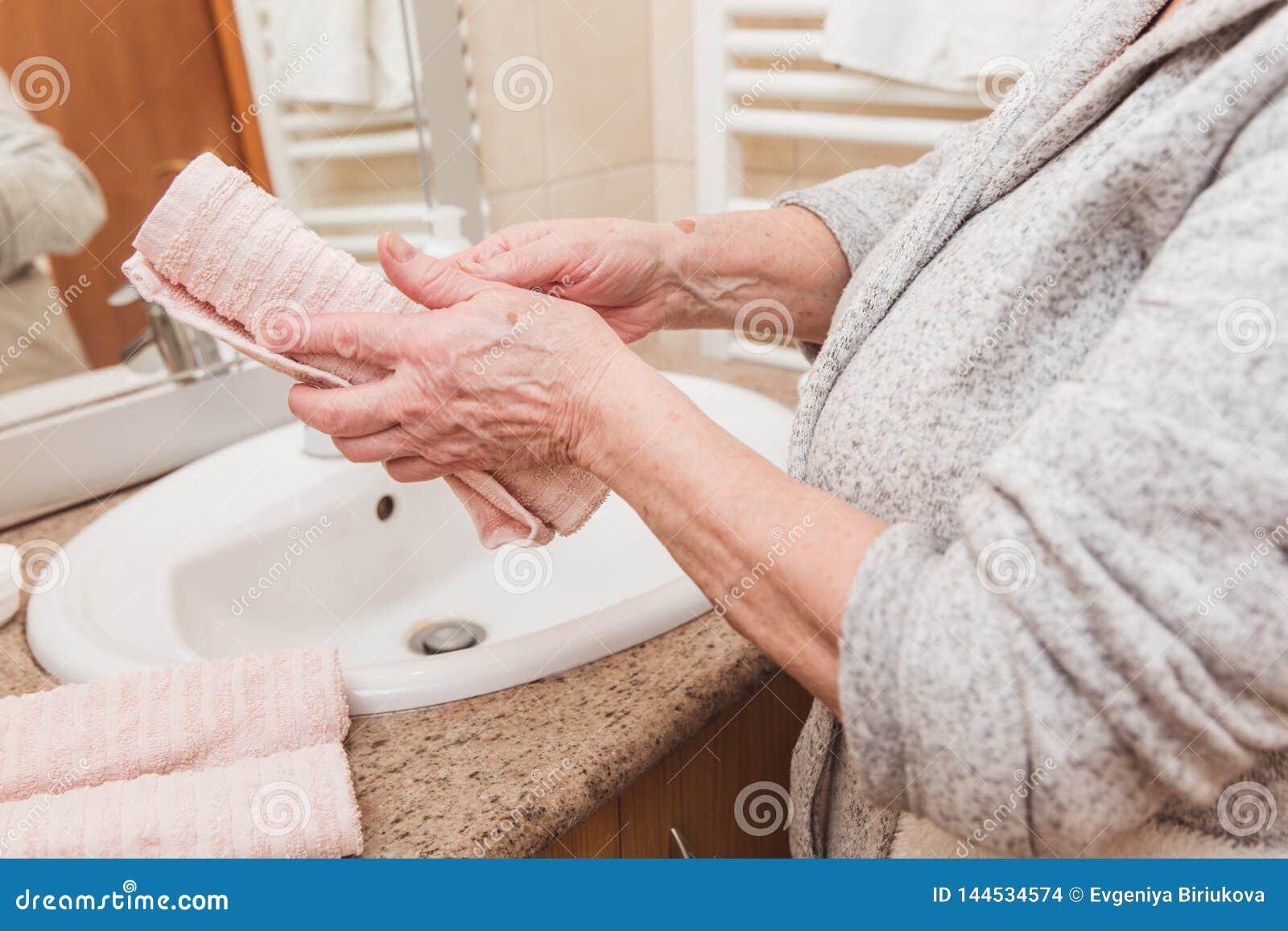 资深妇女抹她的手与一块毛巾在早晨时间的卫生间,特写镜头里